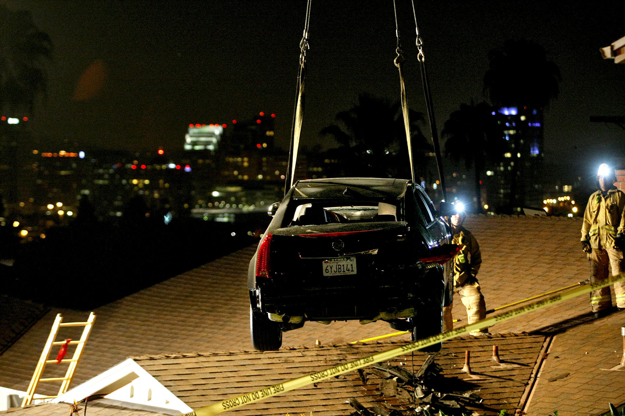 A car is removed by crane from the roof of a home on the 400 block of Audraine Dr. in Glendale on Saturday, March 23, 2013. The driver told police he lost his brakes. The car went onto a neighbor's lawn and launched off onto the roof of the lower house down the street.