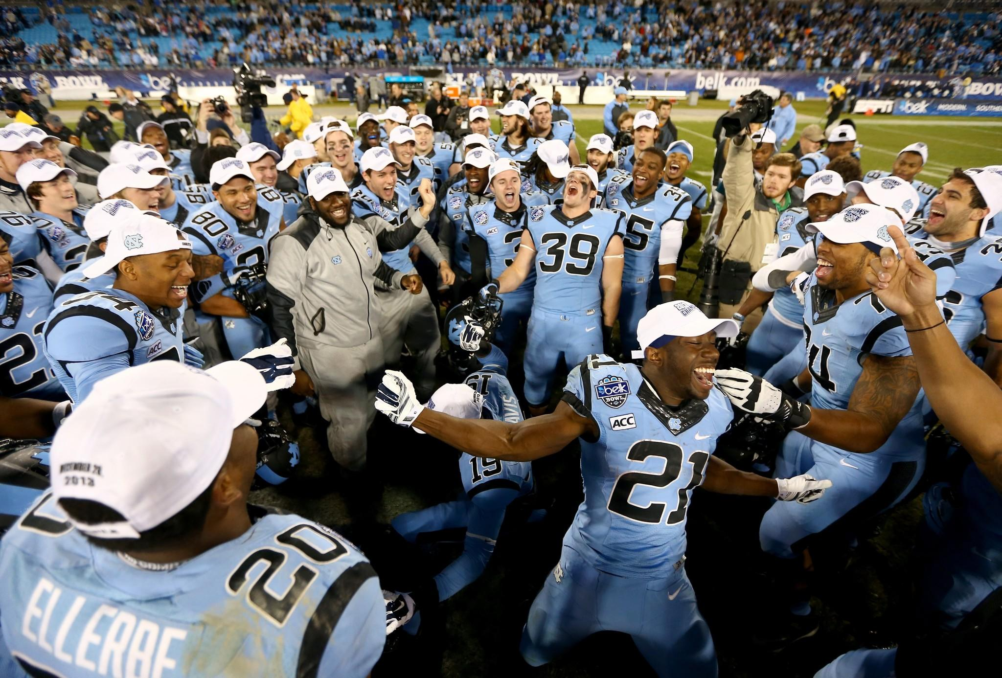 Romar Morris celebrates with teammates after defeating Cincinnati 39-17 at Bank of America Stadium.