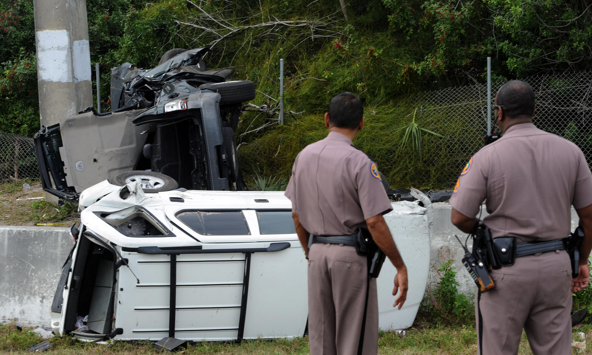 Florida Highway Patrol Troopers look over the wreckage of two cars late Saturday morning on I-95 southbound on the approach to the Lantana Road exit.