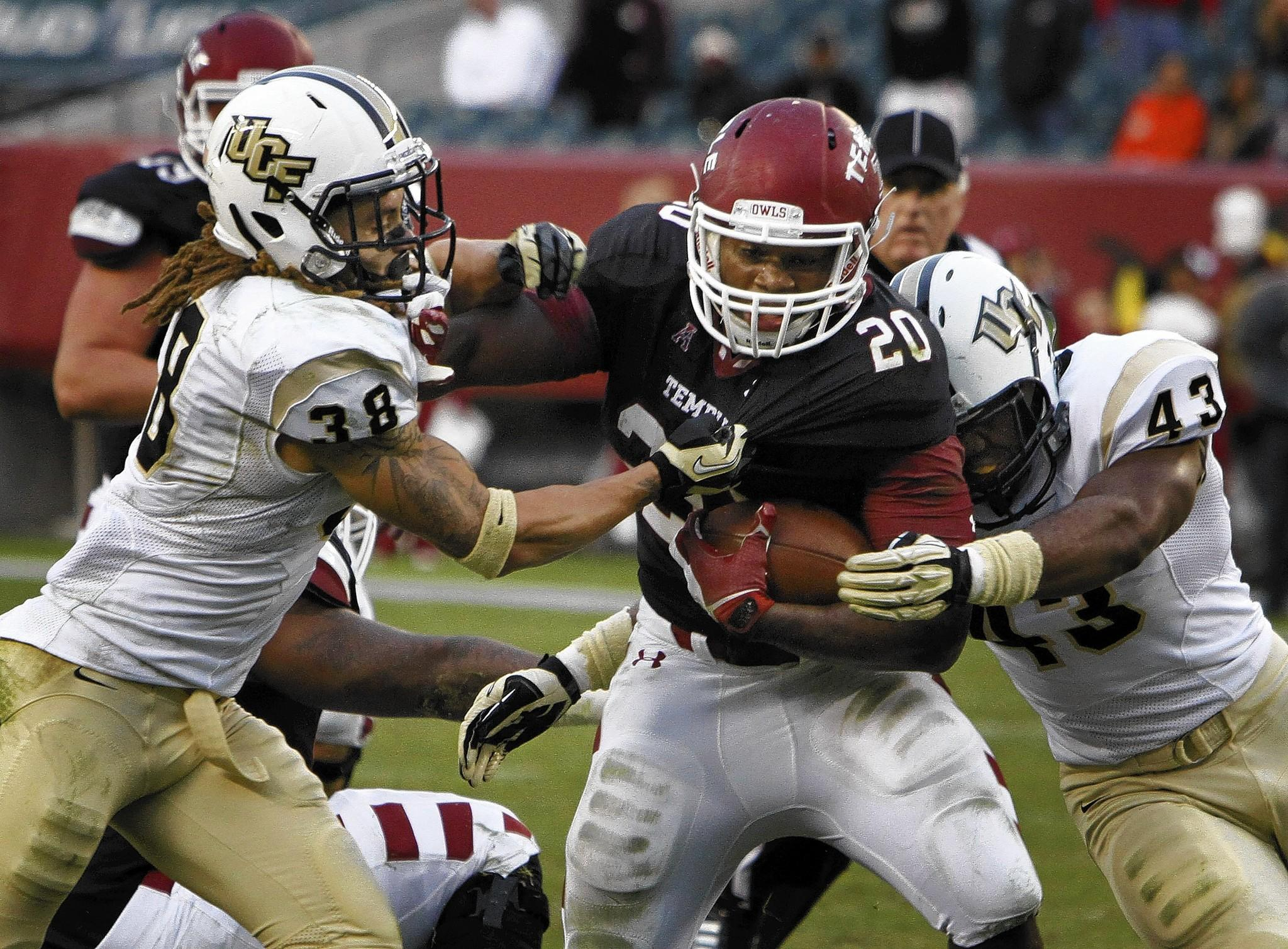 Kenneth Harper, center, of the Temple Owls runs through Jordan Ozerities, left, and Deondre Barnett, right, of the Central Florida Knights in Philadelphia on Saturday, Nov. 16, 2013. (Michael S. Writz/Philadelphia Inquirer/MCT) ORG XMIT: 1145681 ** OUTS - ELSENT, FPG, TCN - OUTS **