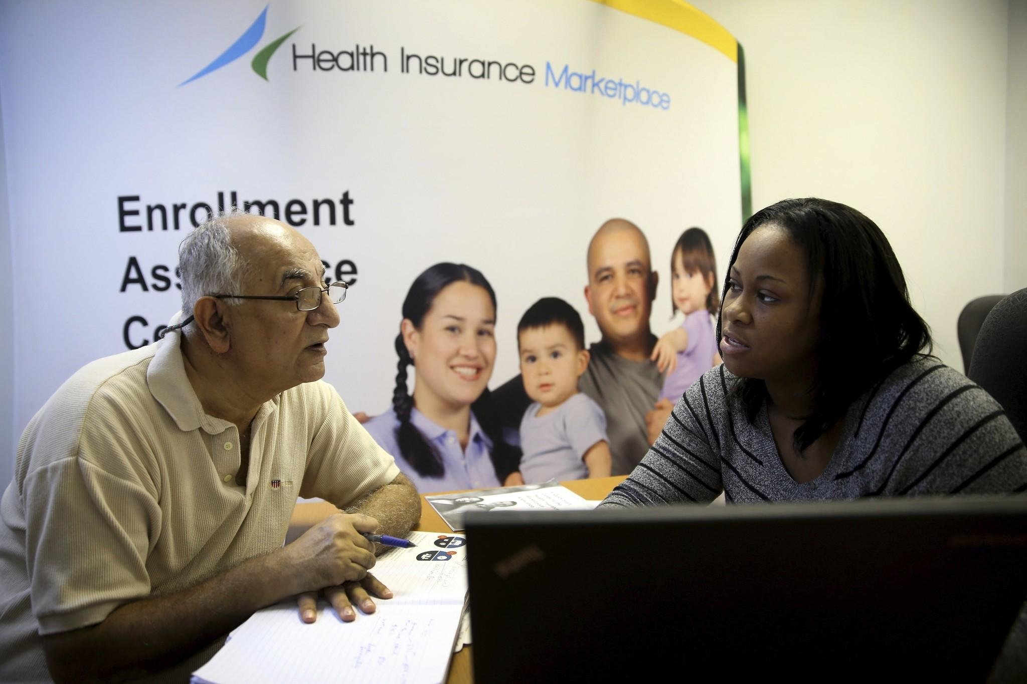 Narendra Parmar sits with Certified Enrollment Specialist, Laquanda Jordan, as he finishes the process of picking and signing up for health insurance through the Affordable Care act at a Miami Enrollment Assistance Center on December 23, 2013 in Miami, Florida. Today is the deadline for people to enroll in a plan that would start January 1st.