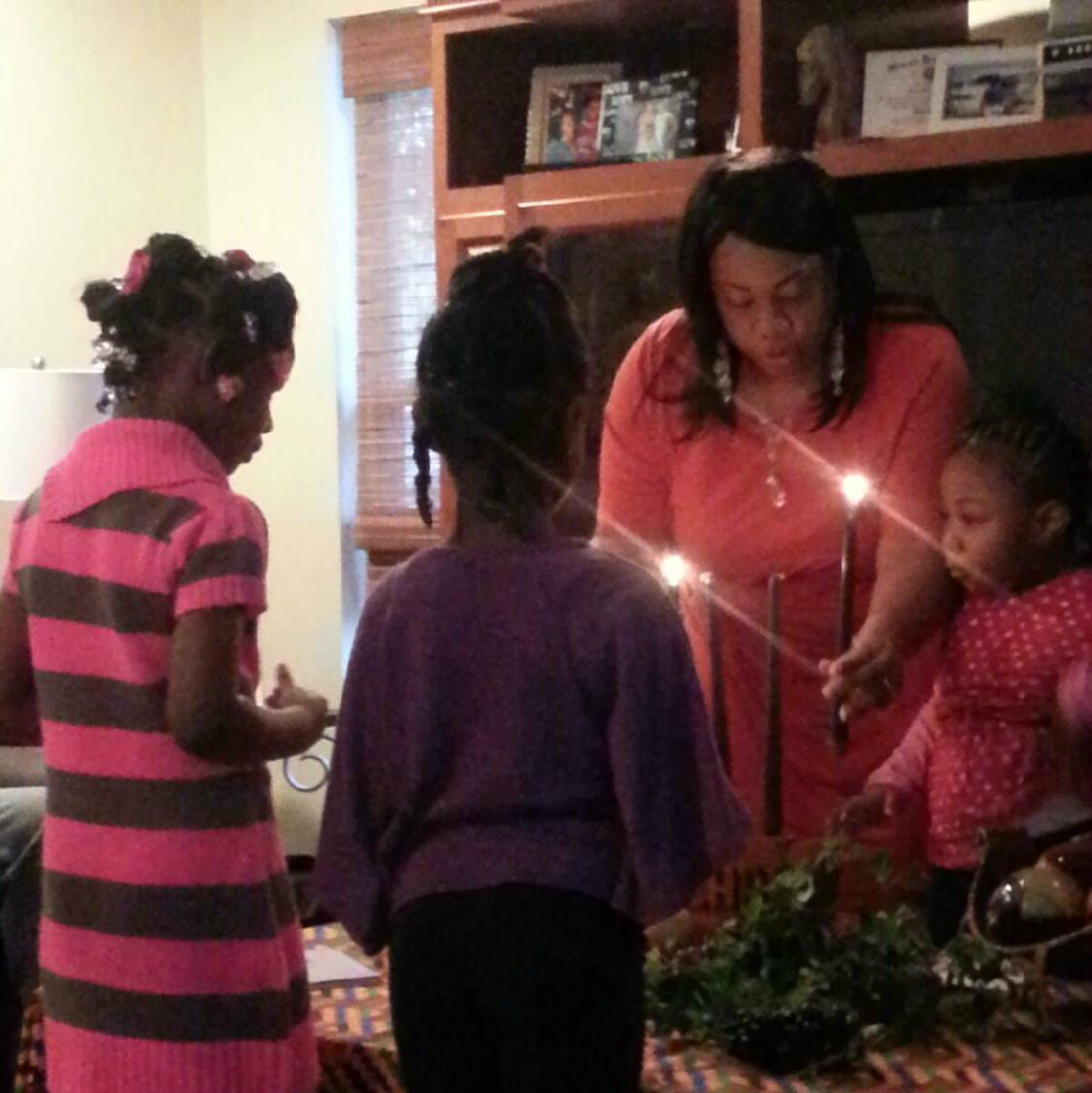 Regina Freeman and three younger members of her family light candles together in honor of the fourth day of Kwanzaa.
