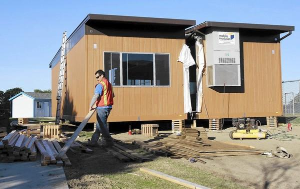 A crewman works on the portable and permanent new classrooms to make way for the increased enrollment at Thurston Middle School.