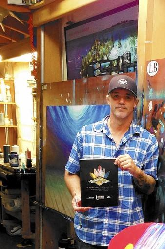 Wyland, in his studio, displaying the program for Surfboards on Parade.