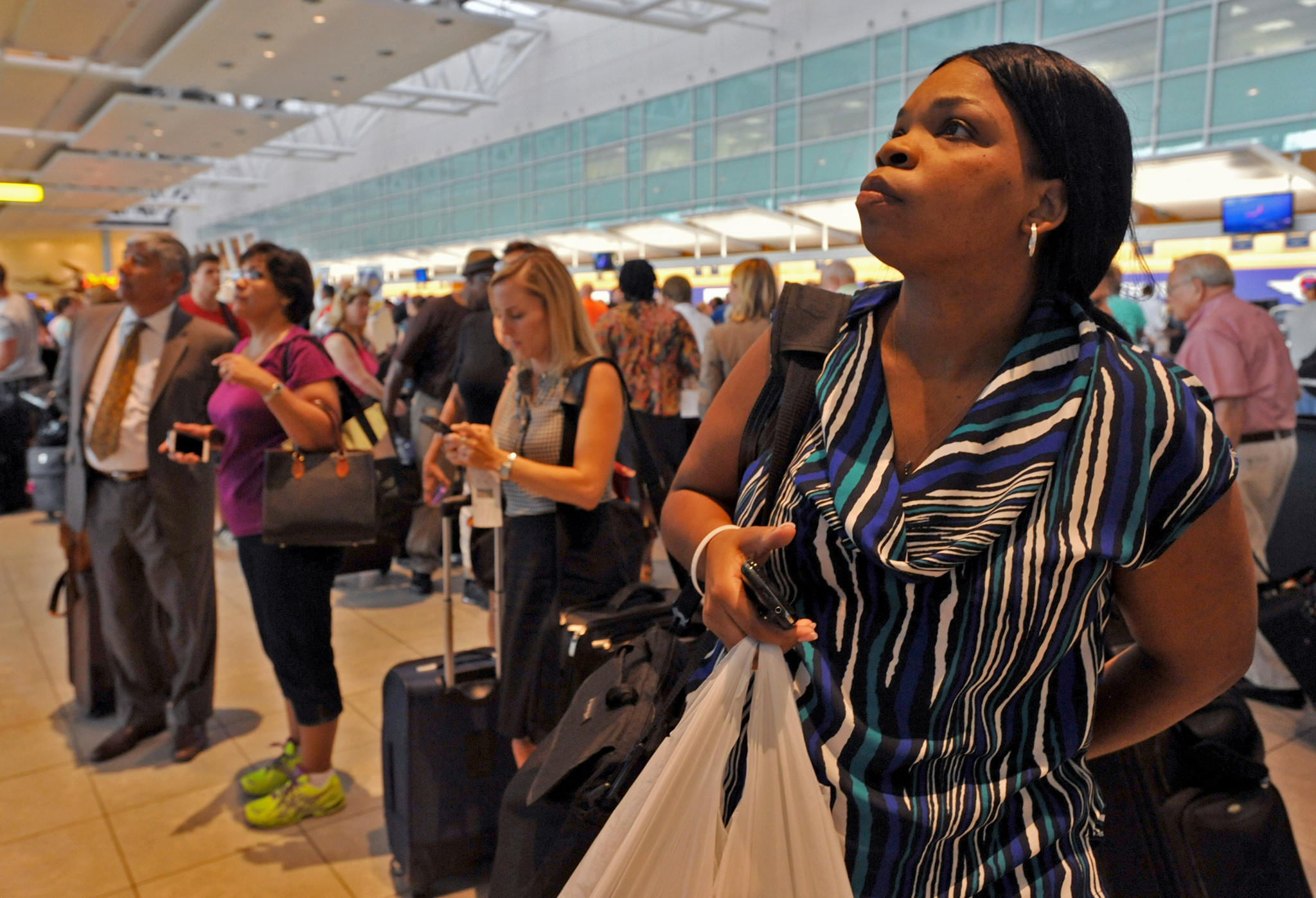 Nakia McGhee of Houston checks the departure board after her 4:45pm flight on Southwest Airlines was cancelled because a severe thunder storm in June.