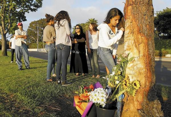 An unidentified girl writes on the tree where a car crashed, killing five Irvine teens on Memorial Day along Jamboree Road in Newport Beach.