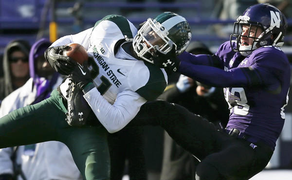 Michigan State cornerback Darqueze Dennard is facemasked by Northwestern wide receiver Mike McHugh while intercepting a pass during a Nov. 23 game. Dennard has proven to be a very valuable asset to the Spartans' secondary.