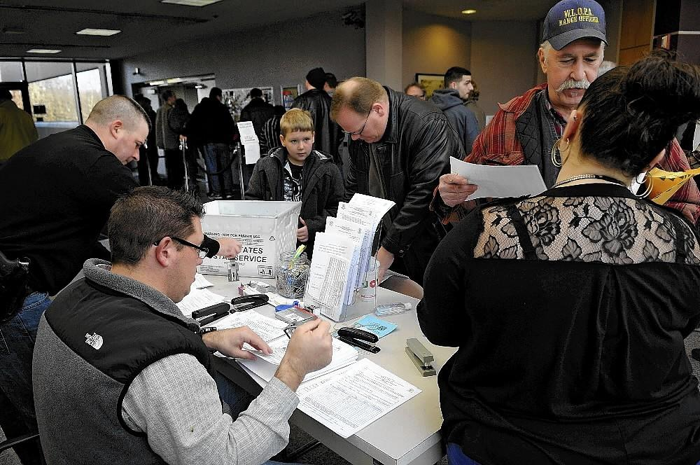 State police personnel are busy helping residents register their firearms and high capacity magazines Friday as new laws starting on January 1, 2014 will make it more difficult to purchase certain items for guns in Connecticut.