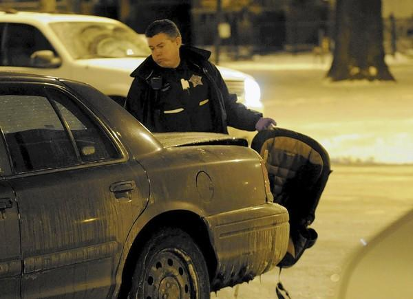 A Chicago police officer places an car seat in a squad car Dec. 11 after infant Lamya Hampton was found unattended, strapped in the car seat, in an apartment in Chicago's Lawndale neighborhood. Lamya later was pronounced dead.