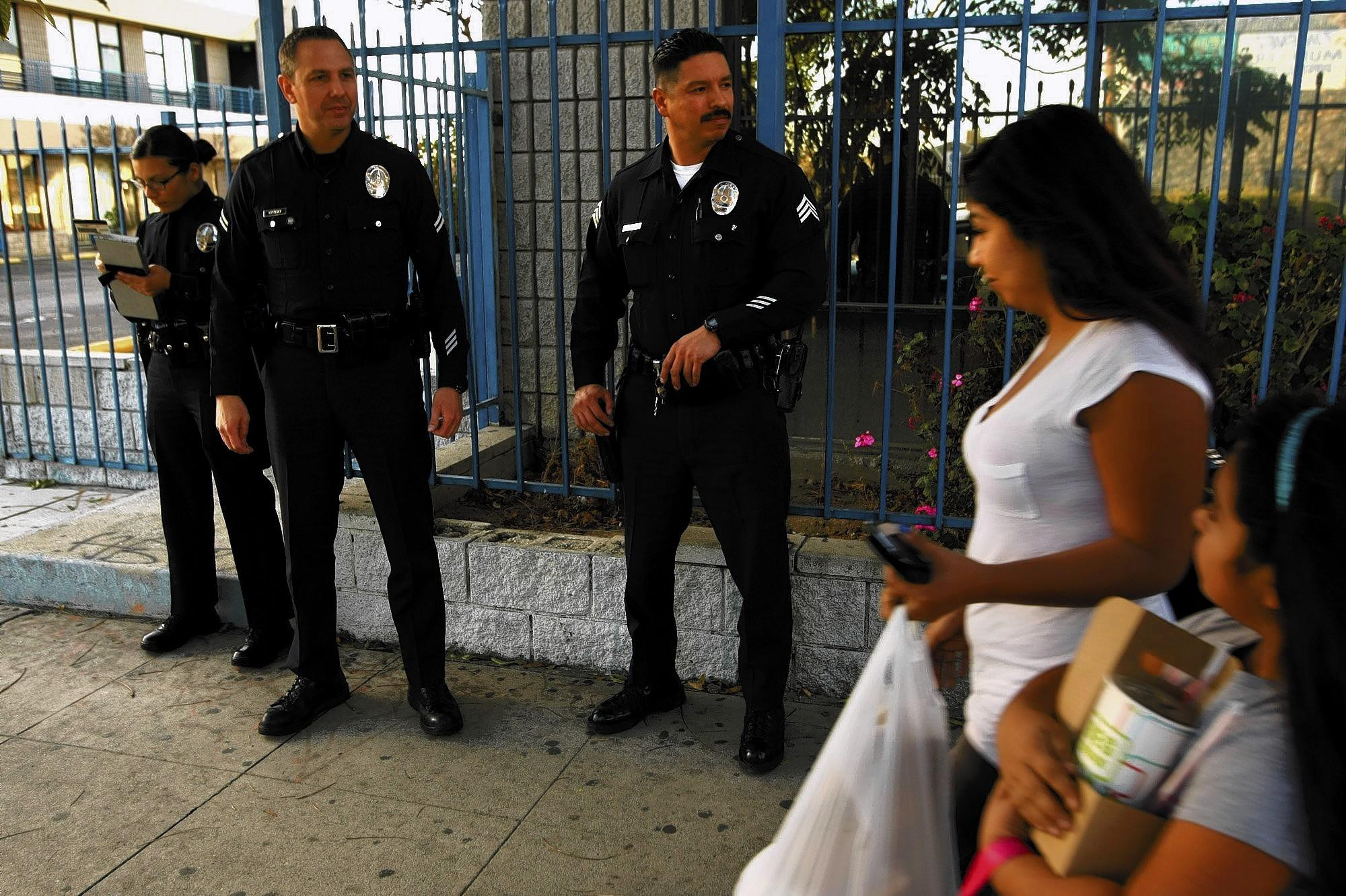 LAPD Officers Cecilia Delgado, left, and Rick Krynsky stand watch with Sgt. Jimmy Balderas as a family passes by on Van Nuys Boulevard in Pacoima. As crime rates in Los Angeles have fallen, police say the decline in violence in tough parts of the San Fernando Valley, like Pacoima, has been particularly striking.
