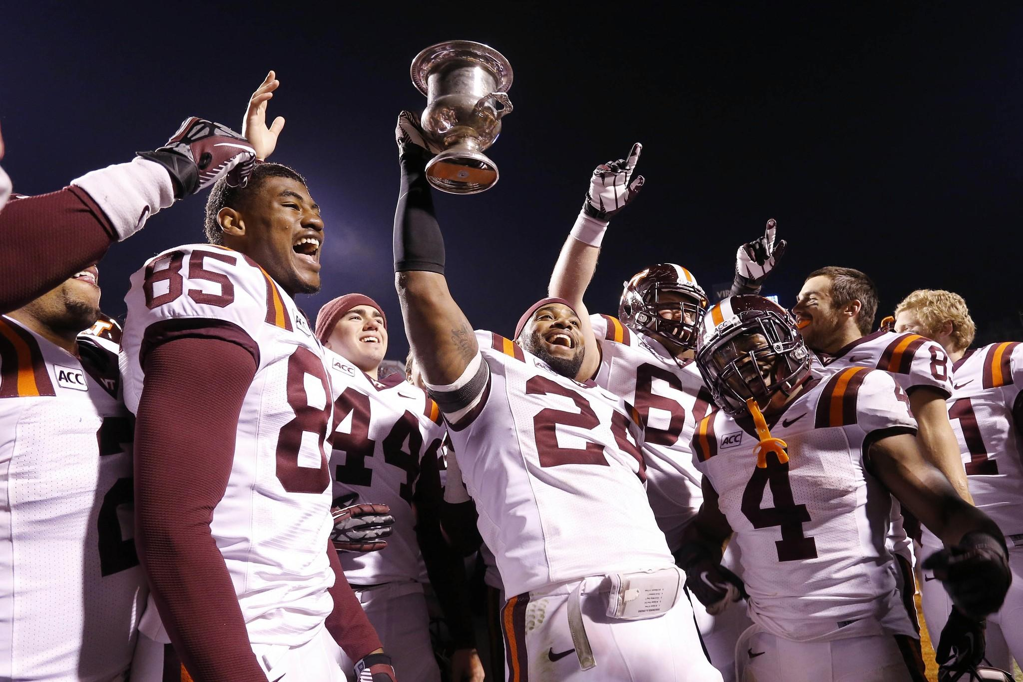 Nov 30, 2013; Charlottesville, VA, USA; Virginia Tech Hokies linebacker Tariq Edwards (24) holds the Commonwealth Cup while celebrating with teammates after their game against the Virginia Cavaliers at Scott Stadium. The Hokies won 16-6. Mandatory Credit: Geoff Burke-USA TODAY Sports ORG XMIT: USATSI-136404