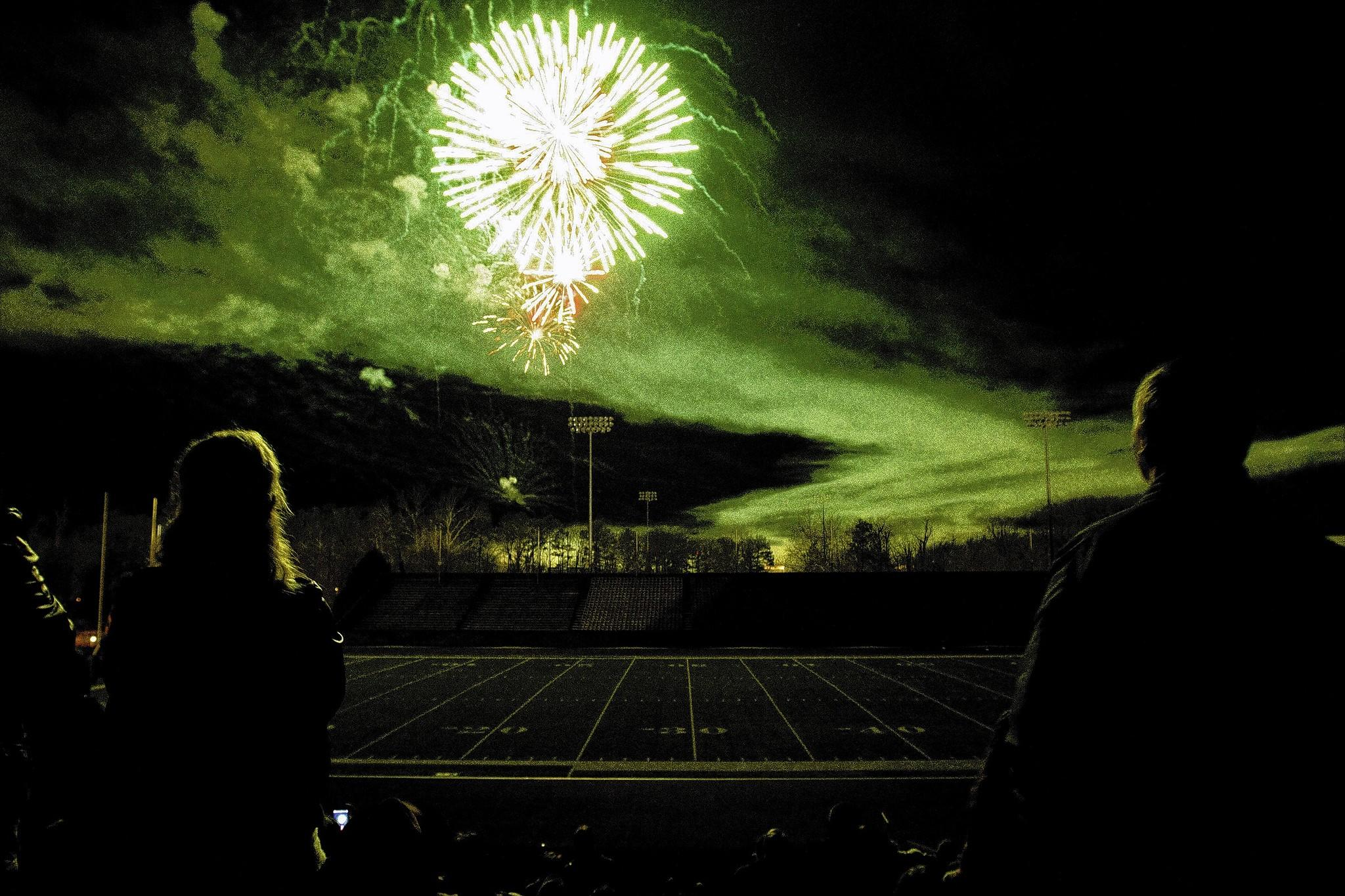 Attendees of FIrst Night Williamsburg 2012 ring in the New Year with a fireworks display at Zable Stadium.