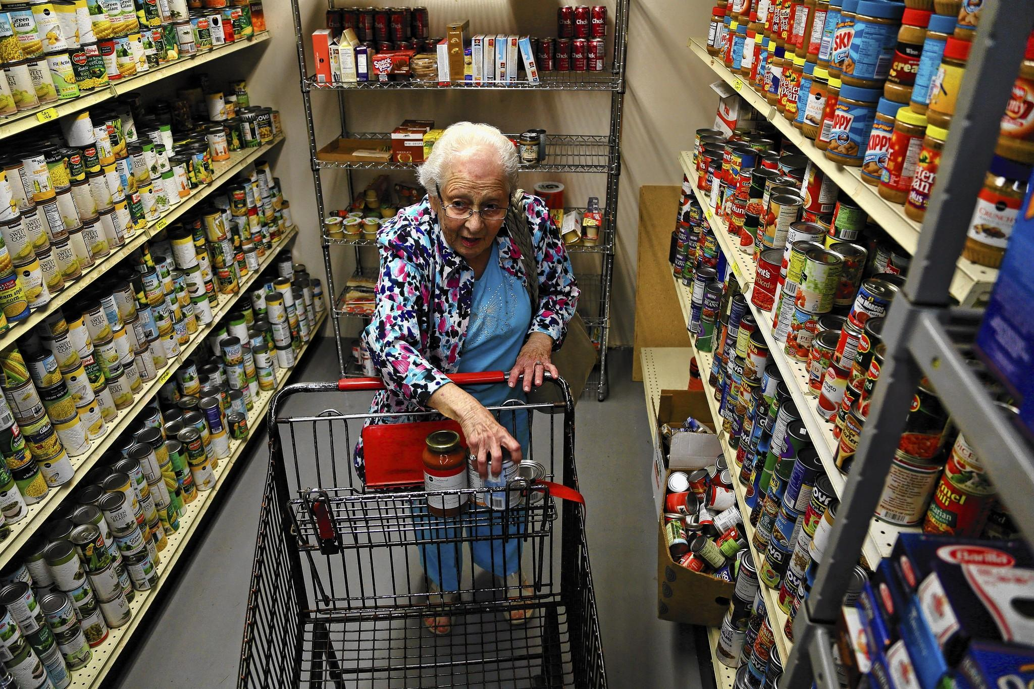 "King's Point resident Elinor Lichten, 87, shops at the Jacobson Family Food Pantry in Delray Beach on Tuesday, Dec. 10, 2013. Lichten said, ""They help keep me alive."" She went on to say, ""It's the seniors that feel the crunch of everything."" Lichten has been a client for the past 4-5 years, but has been shopping at the new Delray location since it opened in November 2012. Food Pantry Operations Manager Dennis Prisant says approximately 75 percent of their clients are seniors."