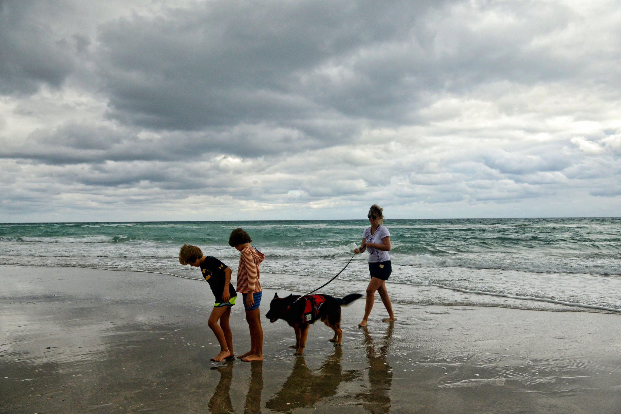 Pali, left, and Kenko Filban enjoy Hallandale beach with their mother, Susie Filban, and her service dog despite the wind and dark rain clouds overhead Tuesday morning.