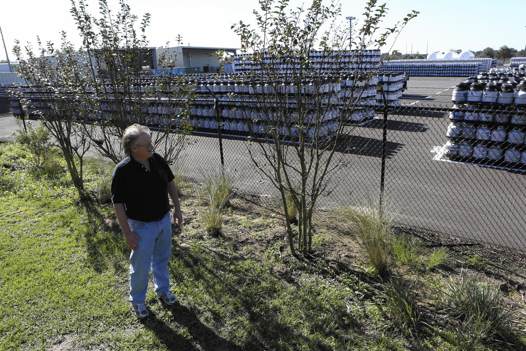 Duane Siebert stands in back of his business just feet from the Blue Rhino propane plant, which in December resumed full operations. The plant was damaged by explosions in July.