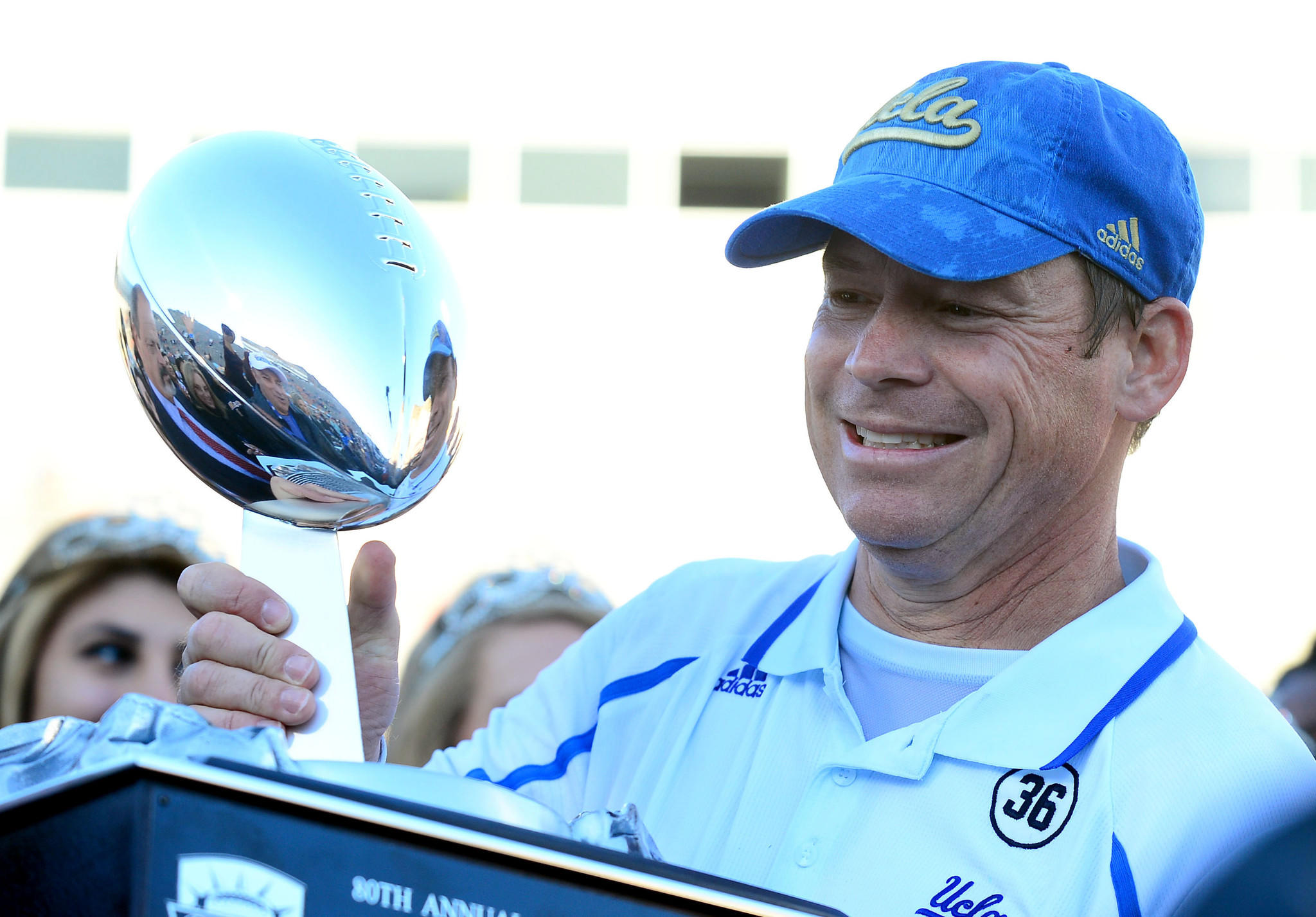 UCLA coach Jim Mora holds the 2013 Sun Bowl trophy after defeating Virginia Tech 42-12 at Sun Bowl Stadium.