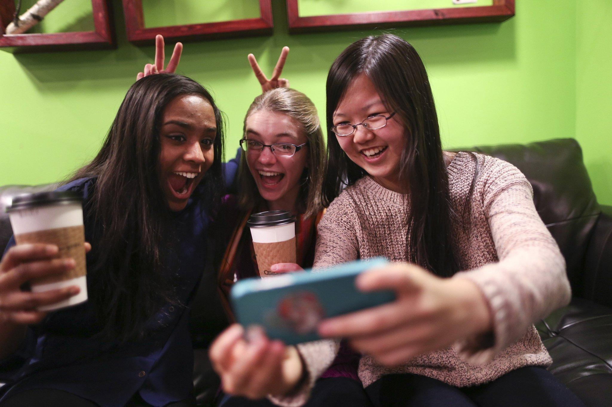 """Friends Amrita Mohanty, 16, from left, Marta Williams, 16, and Michelle Mao, 15, take a Snapchat """"selfie"""" while having coffee at the Steepery Tea Bar in Woodbury, Minn., Dec. 12, 2013."""