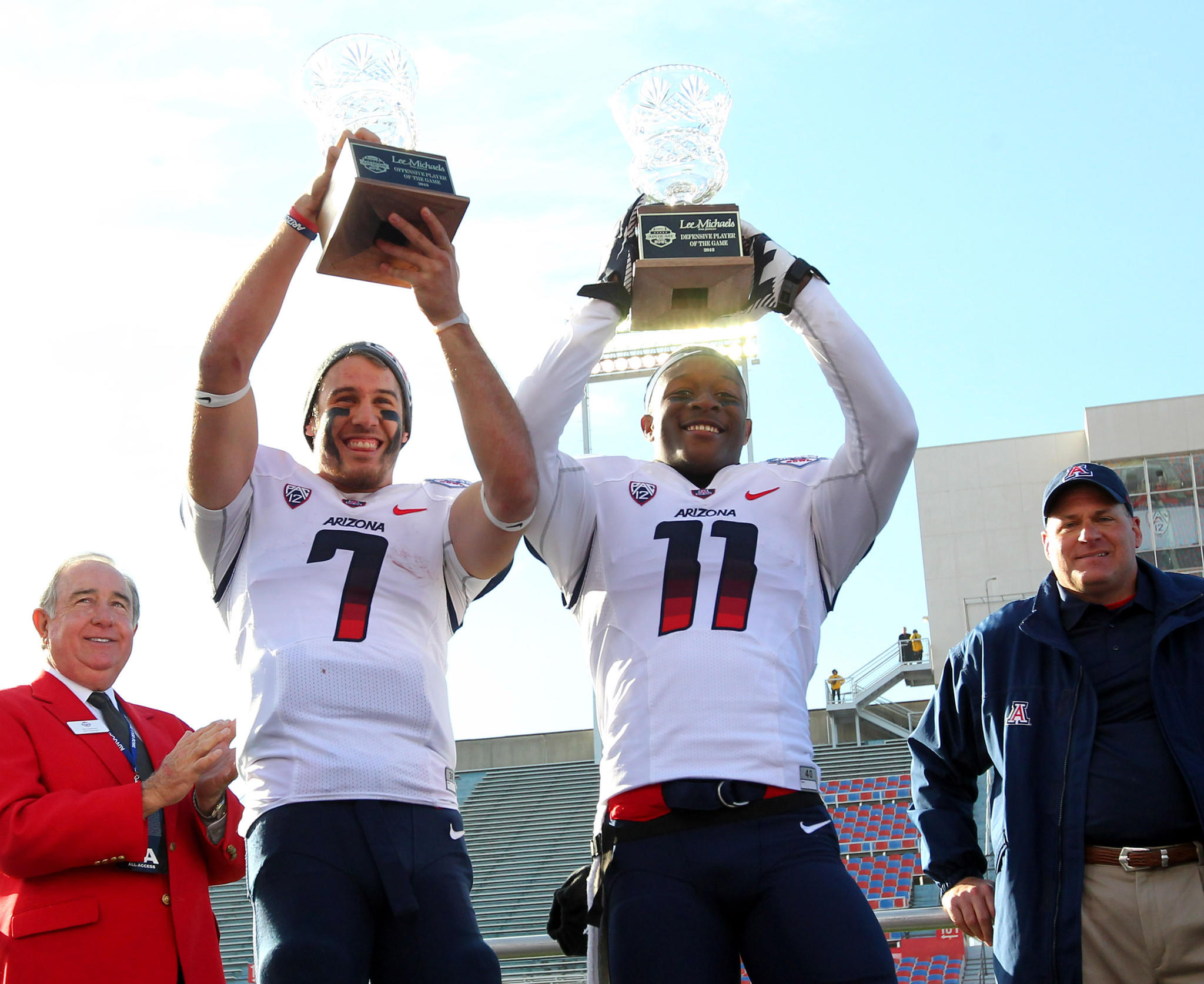 Arizona quarterback B.J. Denker (7) and safety William Parks hold up the offensive player of the game and defensive player of the game trophies at Independence Stadium.