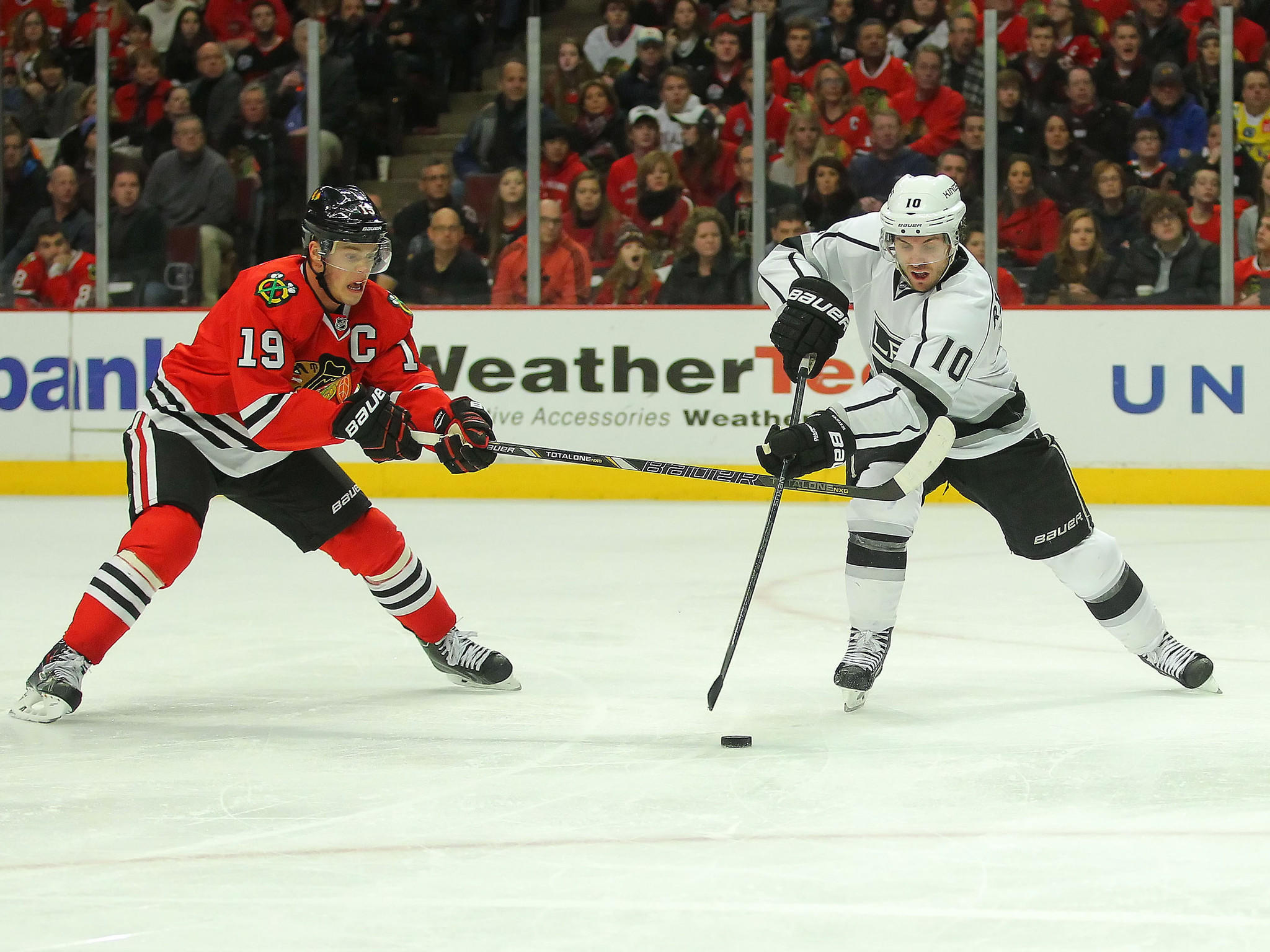The Kings' Mike Richards is checked by Jonathan Toews during the third period at the United Center.