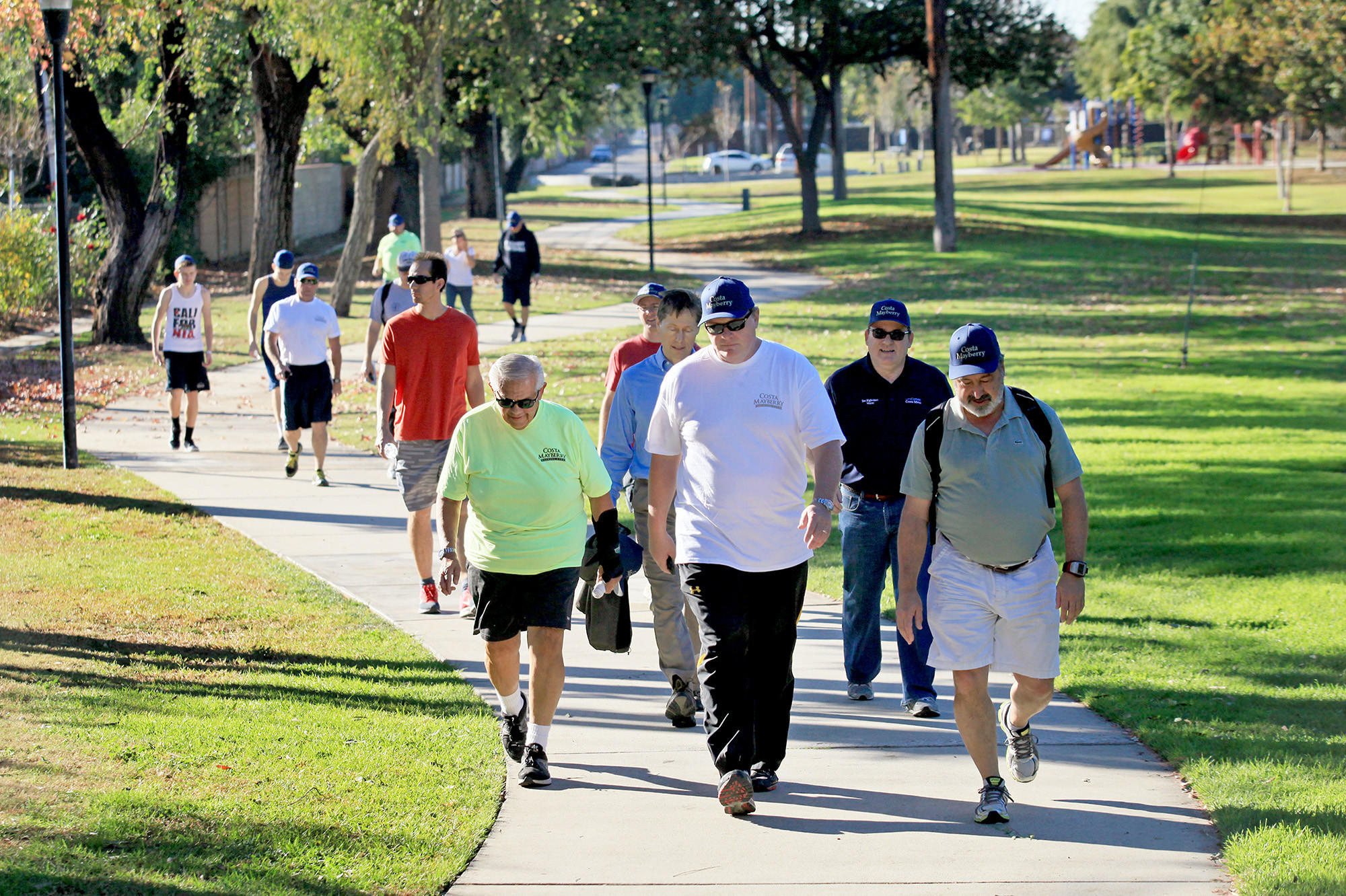 Mayor Pro Tem Steve Mensinger, foreground center, and a dozen other participants stroll through Gisler Park in Costa Mesa on New Year's Eve. The group completed a 5.38-mile walk that started at the Diego Sepulveda Adobe in Estancia Park and ended at Plaza Tower, near South Coast Plaza.