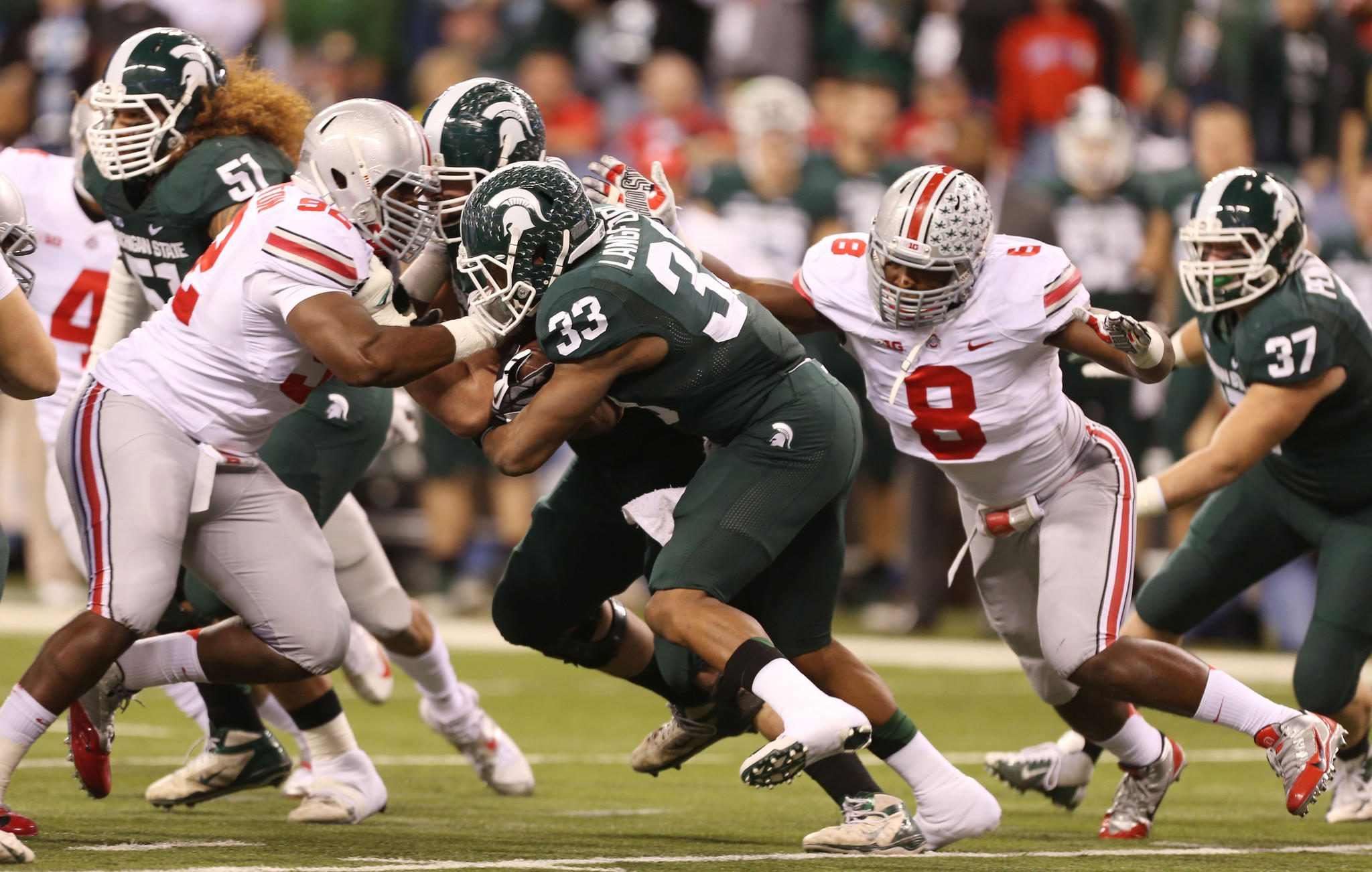 Michigan State running back Jeremy Langford (33) is tackled by Ohio State Buckeyes defensive linemen Noah Spence (8) and Adolphus Washington (92) during the Big Ten Championship game.