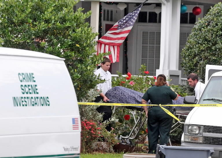 Technicians from the Medical Examiner's Office remove the body after a 15-year-old boy shot his father to death, the Orange County Sheriff's Office said.