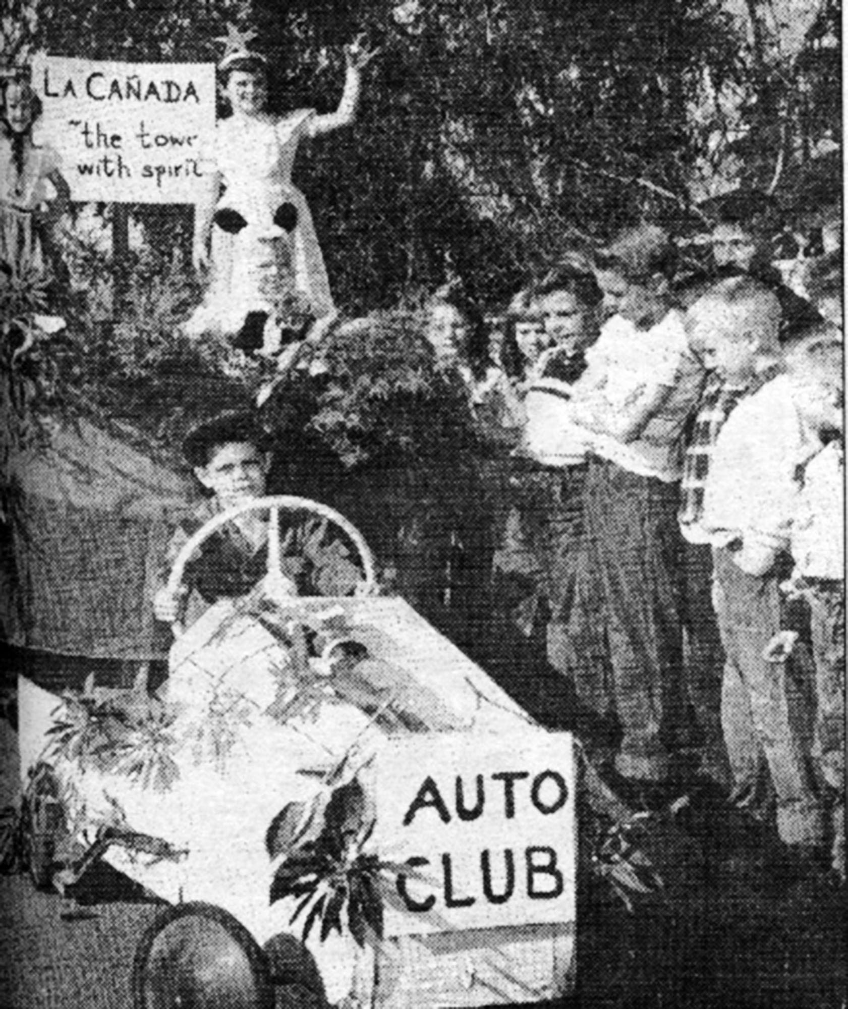 "John Young, 9, behind the wheel of a cart labeled ""Auto Club"" comes to the rescue of a self-built float that was paraded in the Rancho section of town in late December 1953 in homage to Pasadena's Rose Parade. ""La Canada, 'the town with spirit'"" proclaims the sign on the float, on which Christine Roche, 6, and 7-year-old Rayleen Edwards stand."