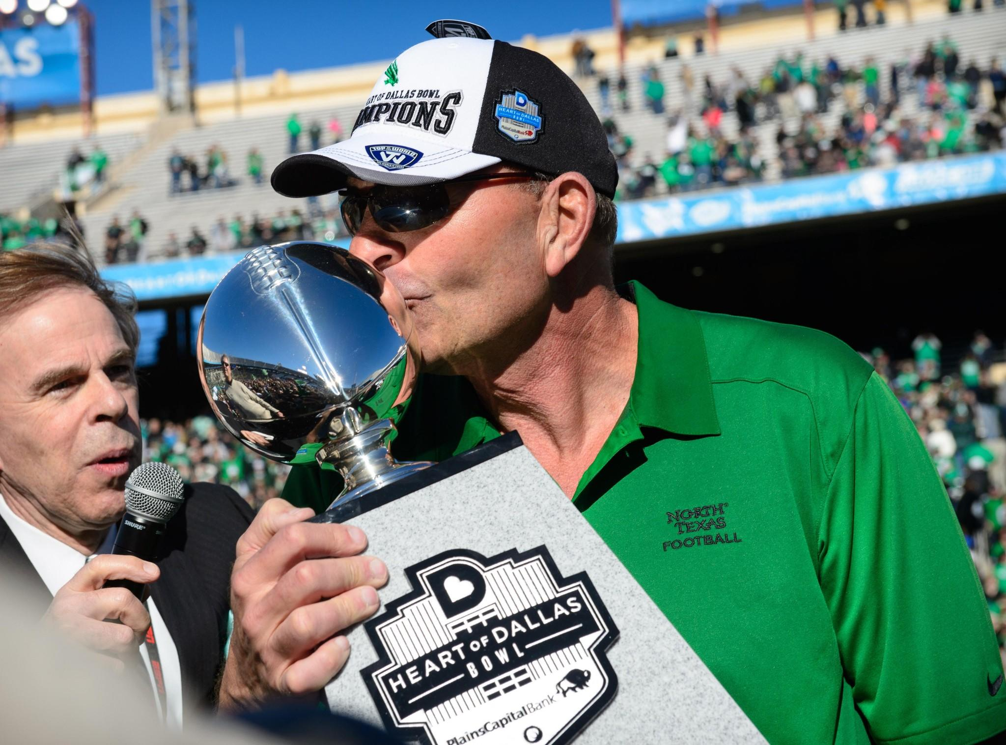 North Texas Mean Green head coach Dan McCarney kisses the Heart of Dallas trophy after the win over the UNLV Rebels at the Cotton Bowl Stadium.