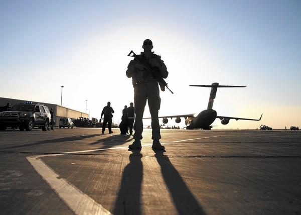 A NATO coalition soldier at an airstrip in Kandahar, Afghanistan. As the U.S. seeks permission to remain in the country for at least another decade, some question what keeping forces there will accomplish.