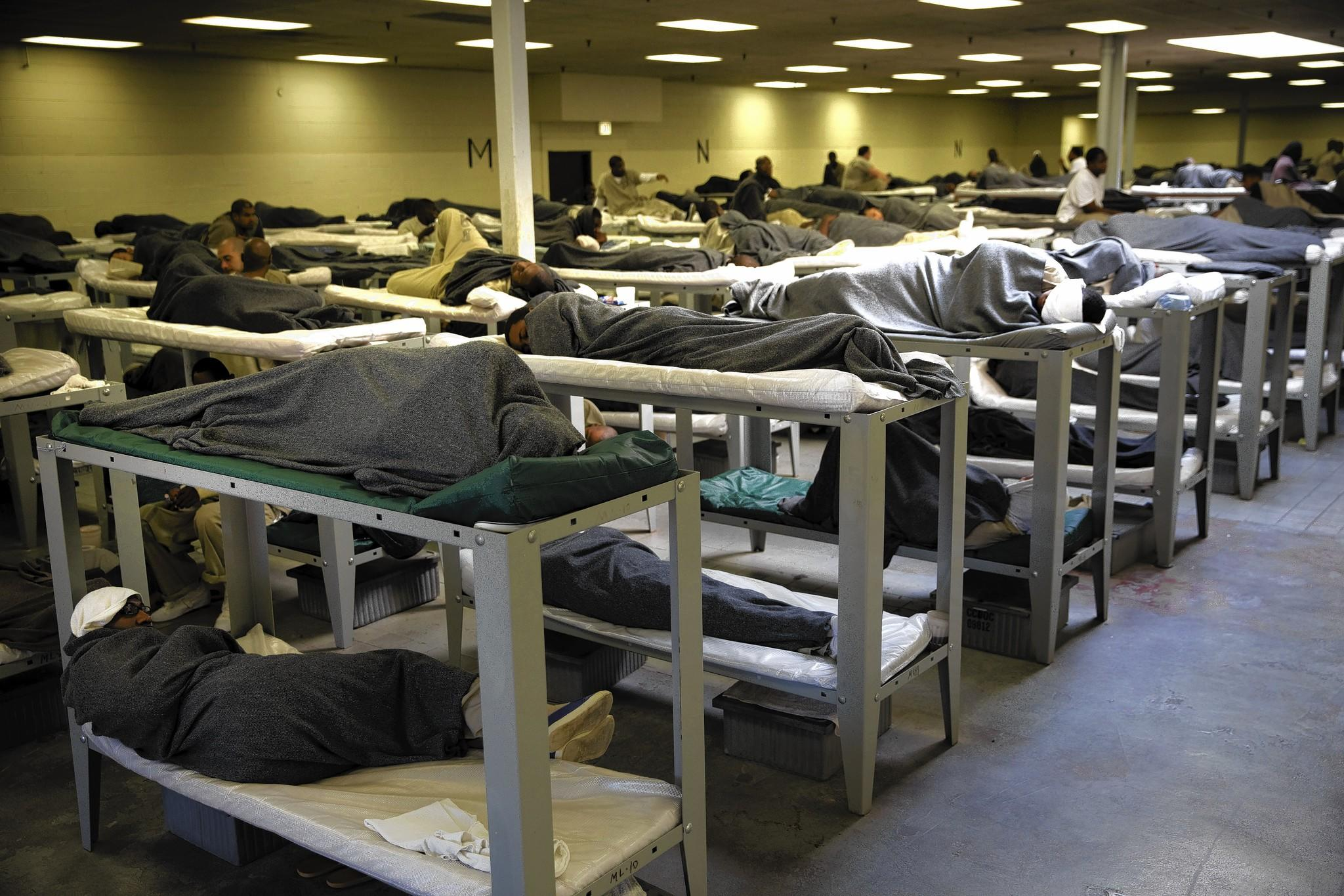 Hundreds of inmates sleep together on bunks in a large room of the Cook County Jail.