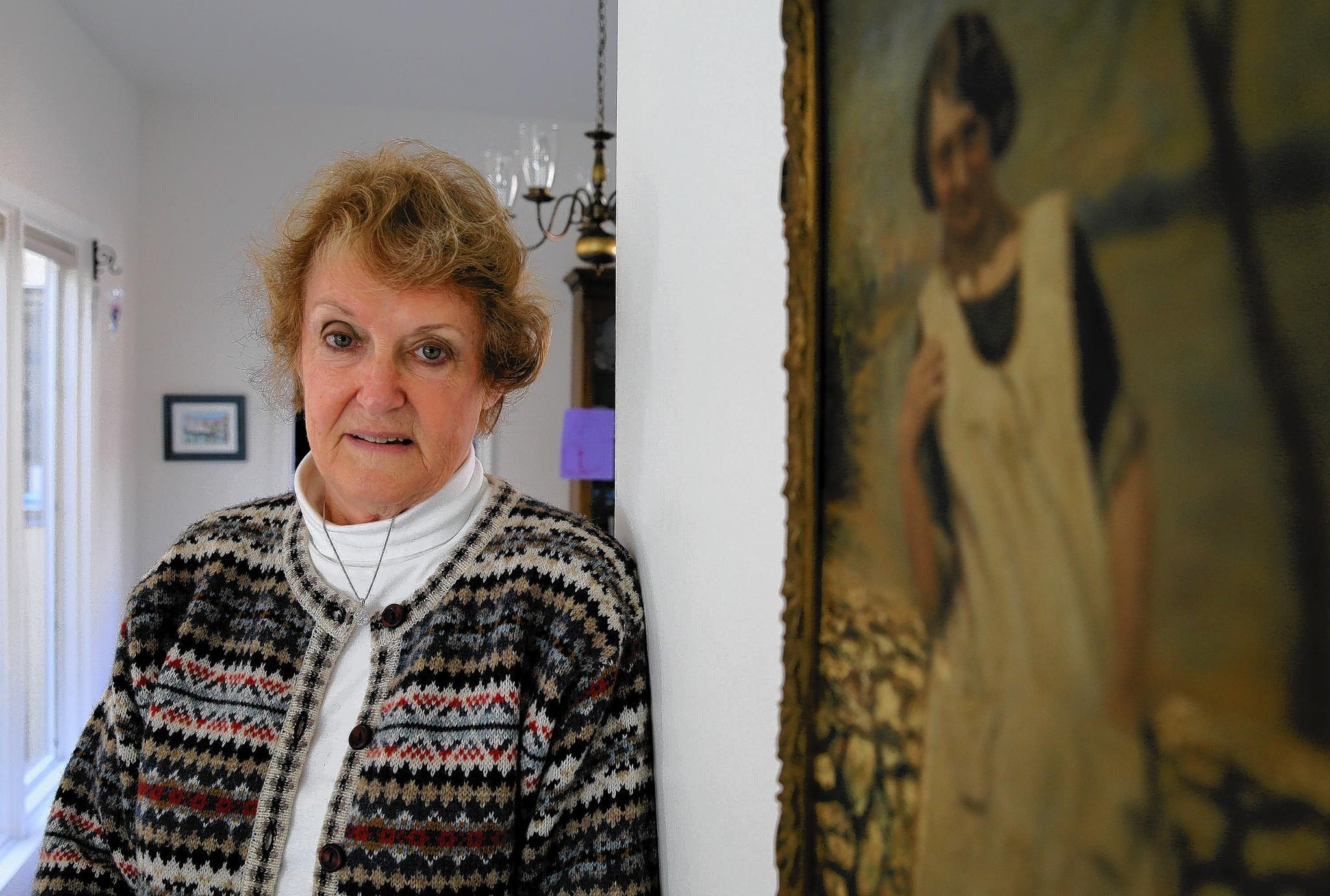 Jacqueline Welch, standing next to a painting of her mother in her Burr Ridge home, is owed $348.98 from an old life insurance policy her mother took out. The insurance company sent the check to an old address, and the money was declared unclaimed property. It ended up in the hands of the state of Florida, and Welch is still waiting for the state to fully process her claim.