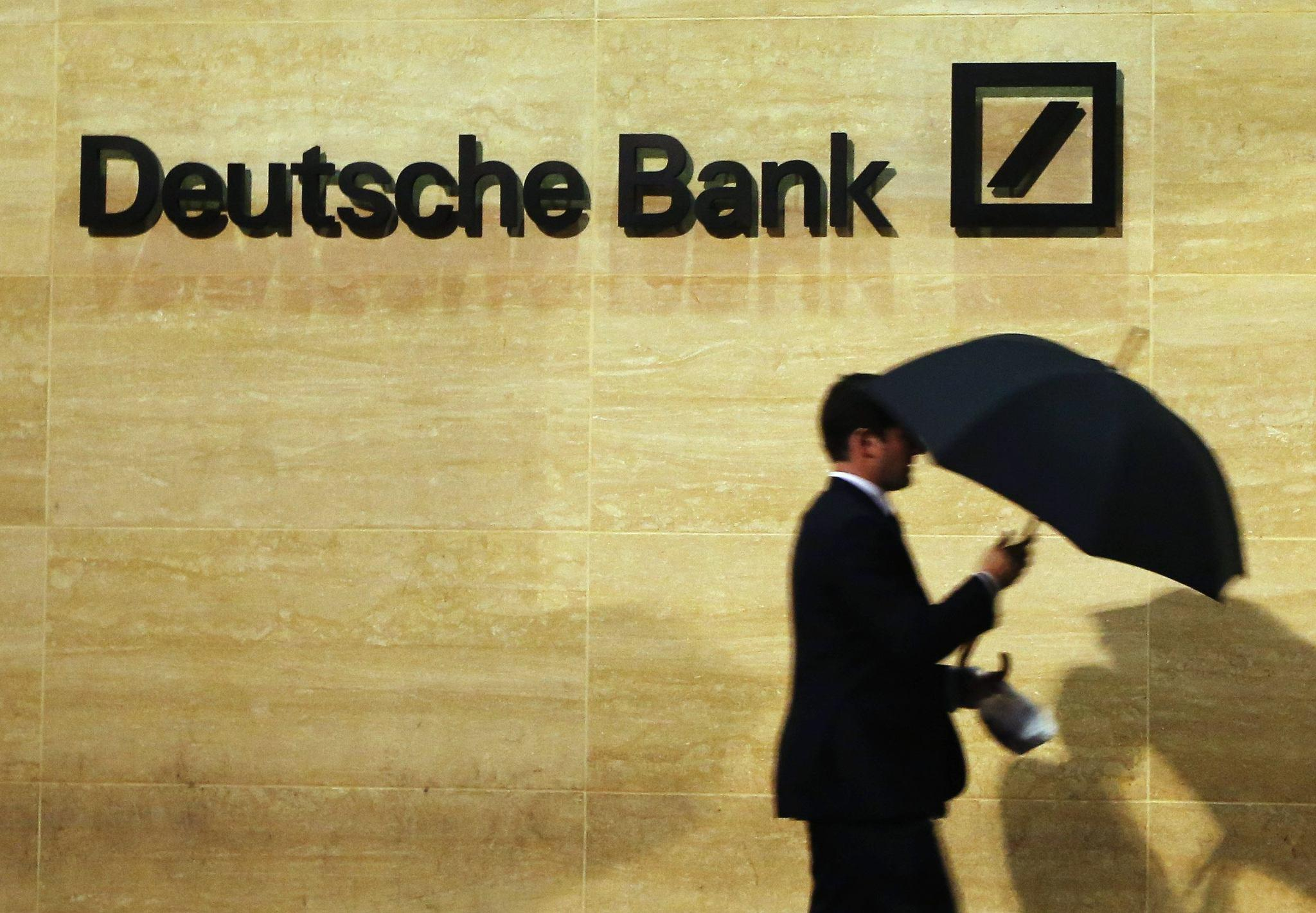 A man walks past Deutsche Bank offices in London on Dec. 5, 2013.