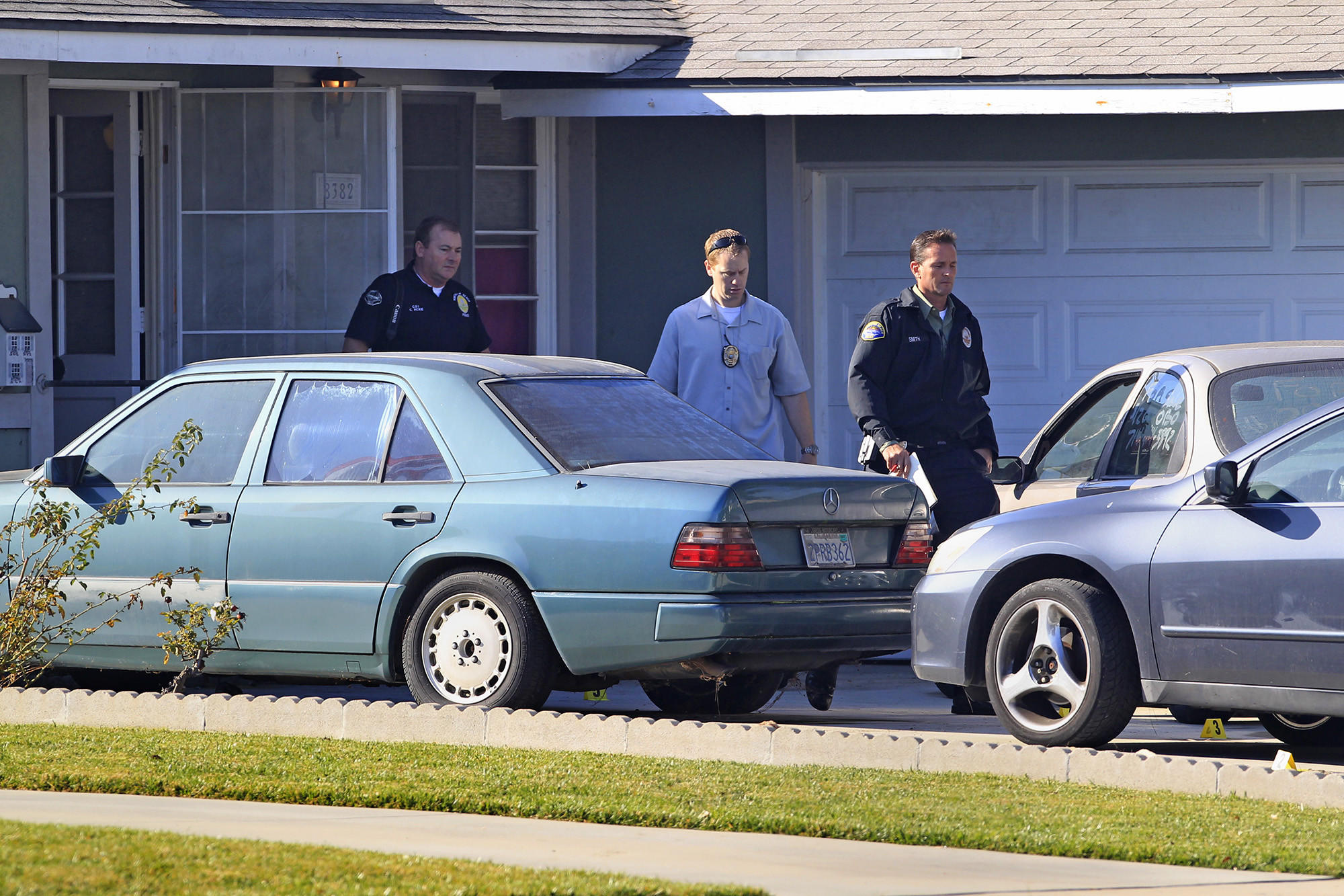 Investigators walk out of a residence in the 8300 block of Lambert Drive in Huntington Beach, where a man was shot multiple times early Thursday morning.