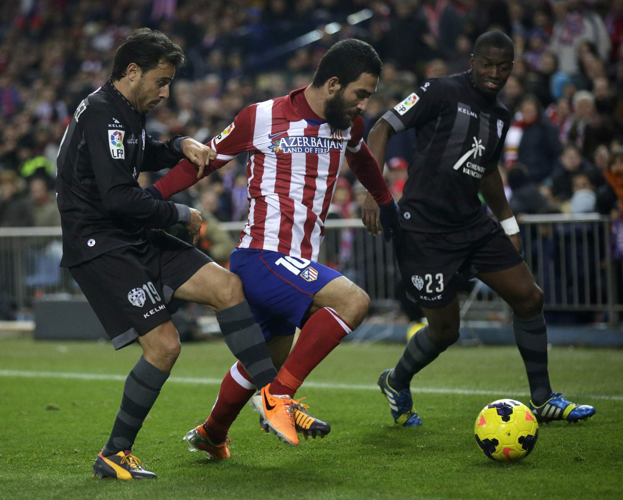 Atletico Madrid's Turan Arda (C) controls the ball between Levante's Pedro Lopez (L) and Papa Diop during their Spanish first division soccer match at Vicente Calderon stadium in Madrid December 21, 2013.