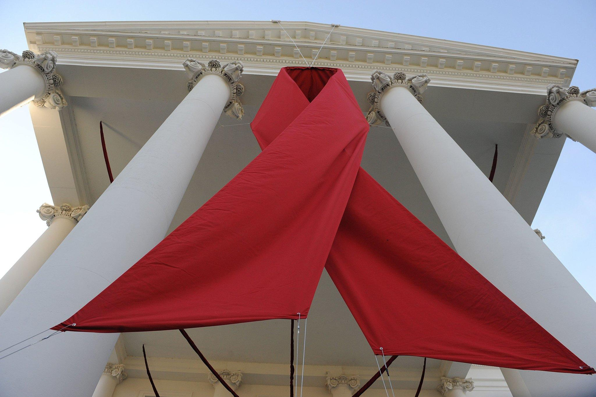 A huge red ribbon hangs on the North Portico of the White House for World AIDS Day on Dec. 1, 2013, in Washington.