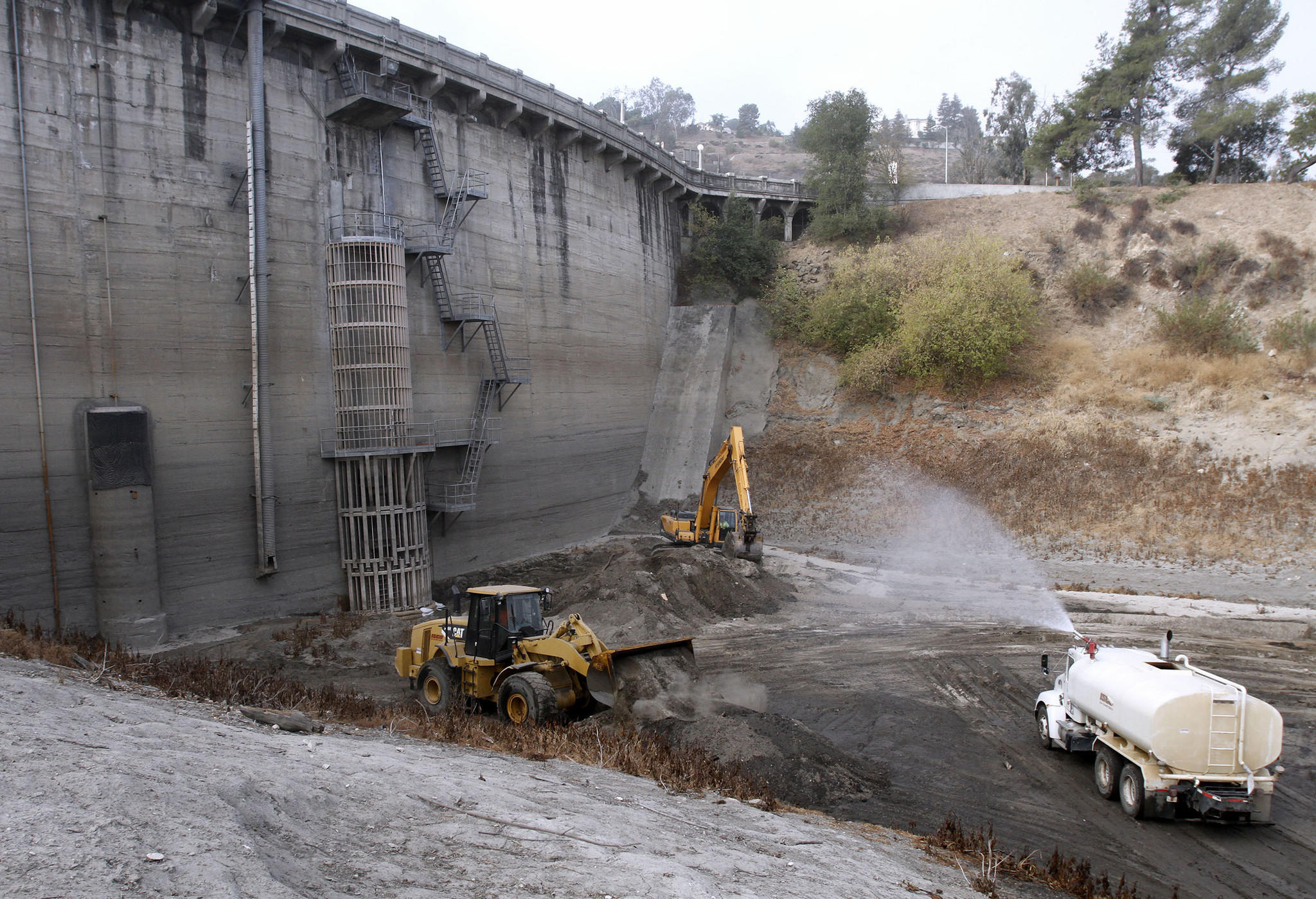 Los Angeles County Department of Public Works crews work to remove dirt from the base of Devil's Gate Dam at Hahamongna Watershed Park in Pasadena on Wednesday, Sept. 18, 2013.