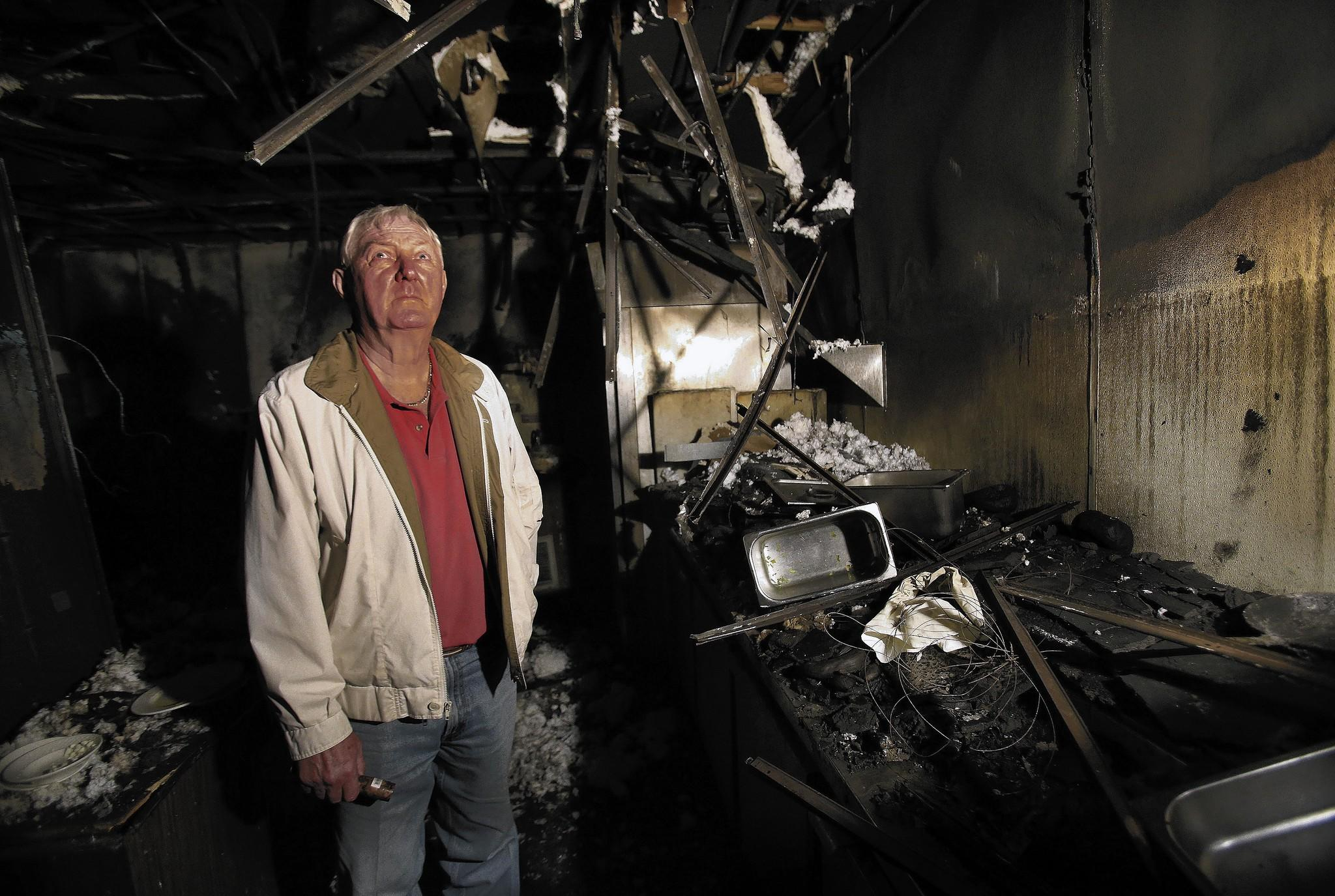 Vic Donahey Jr., founder of the popular Vic's Embers Supper Club, surveys the damage from a major fire that destroyed the restaurant.