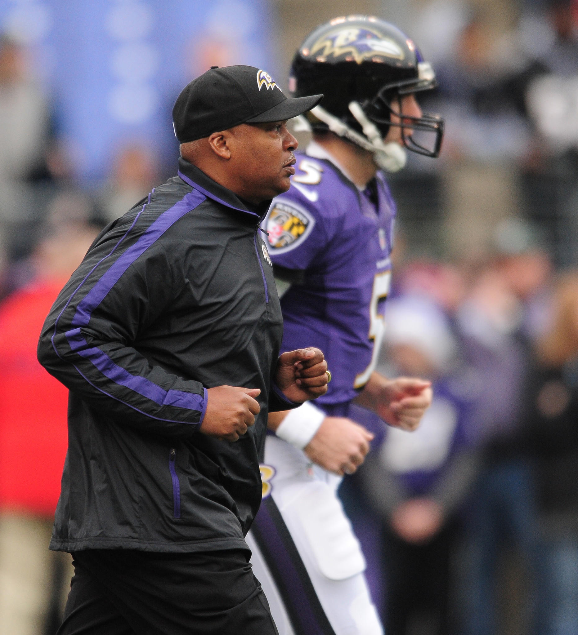Ravens offensive coordinator Jim Caldwell jogs with Ravens quarterback Joe Flacco in 2012.