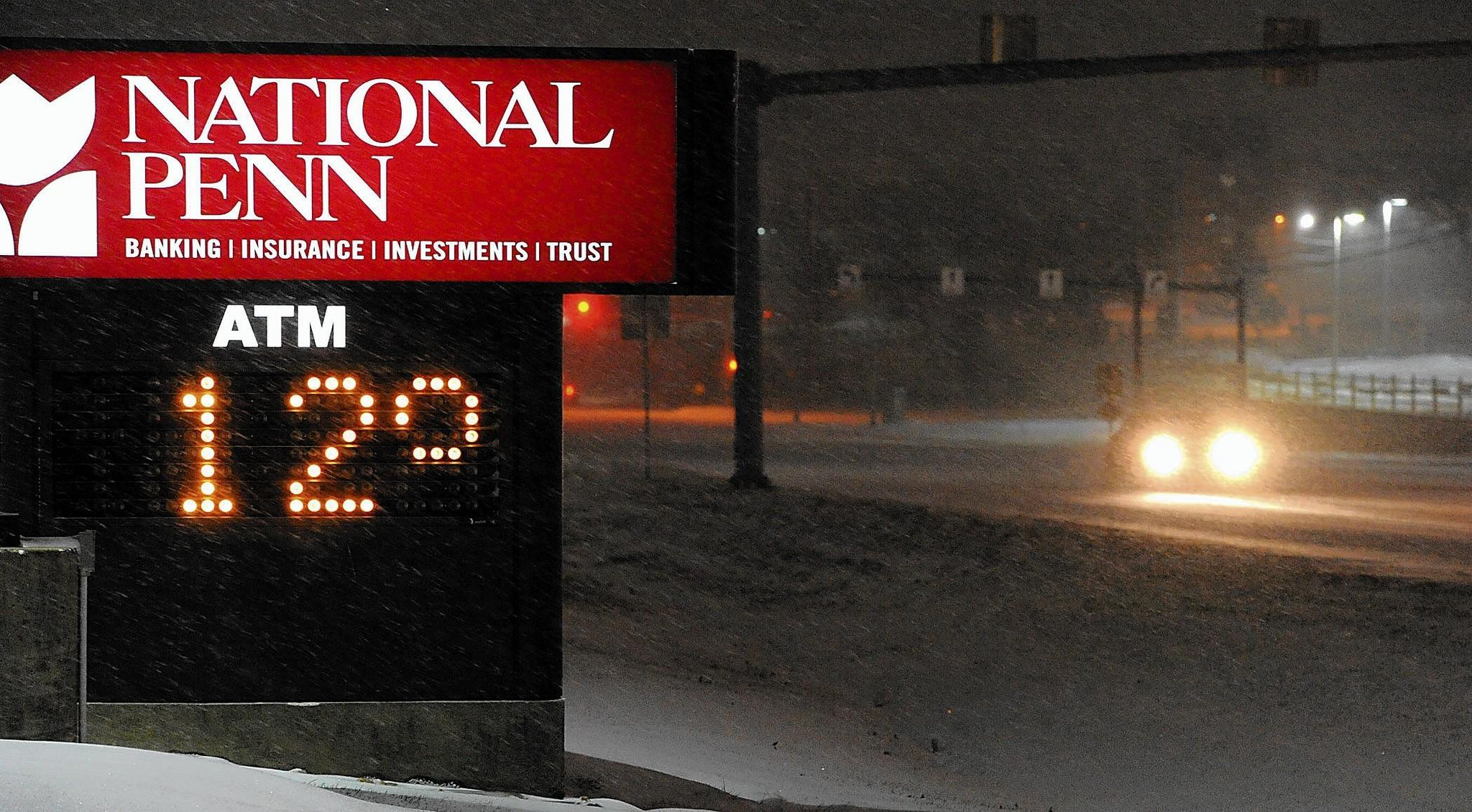The National Penn sign reads 12 degrees as alone vehicle tries to navigate Route 248 in Palmer Township on a snowy Thursday night.