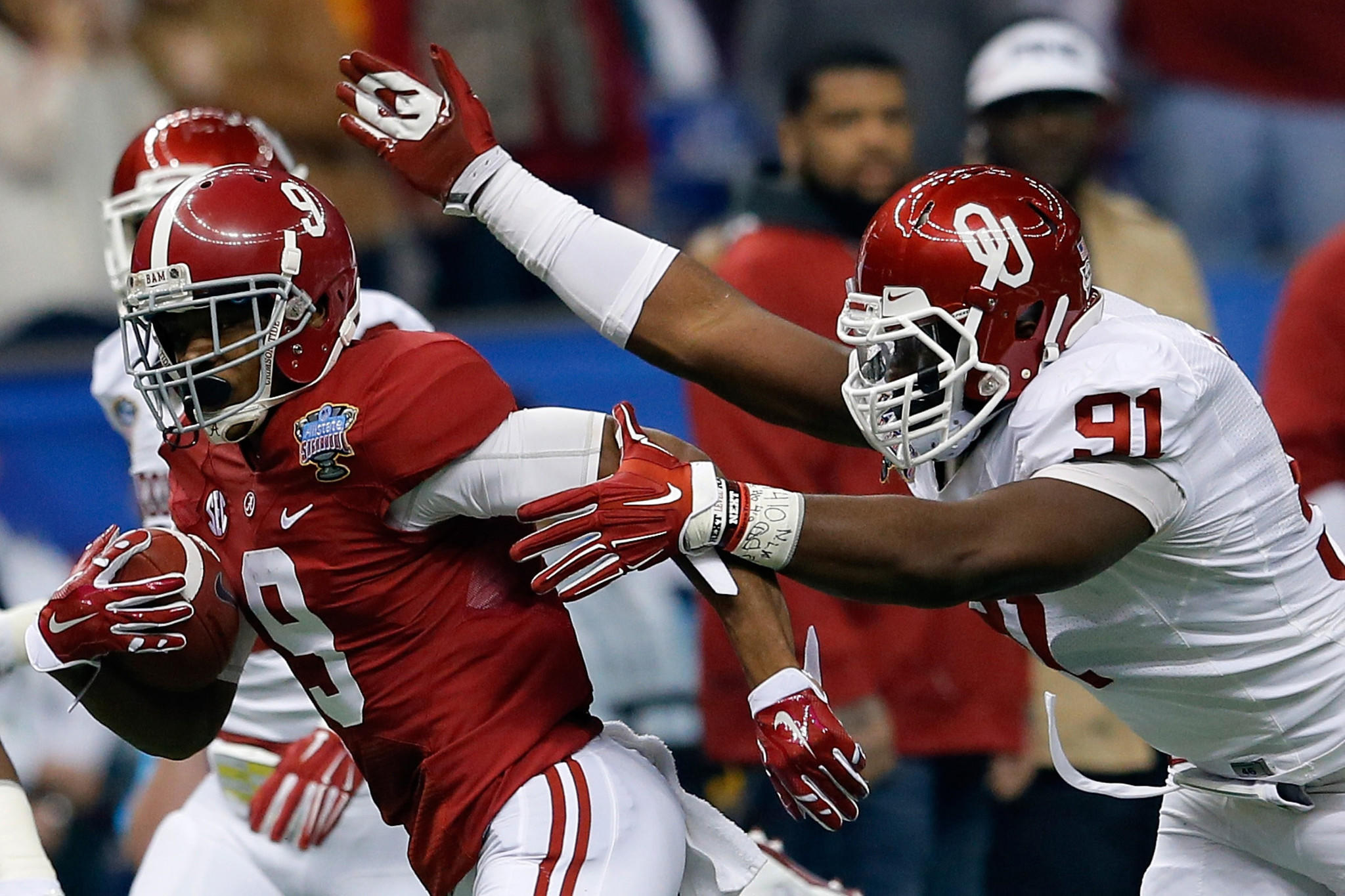 Amari Cooper #9 of the Alabama Crimson Tide is tackled by Charles Tapper #91 of the Oklahoma Sooners during the Allstate Sugar Bowl at the Mercedes-Benz Superdome.