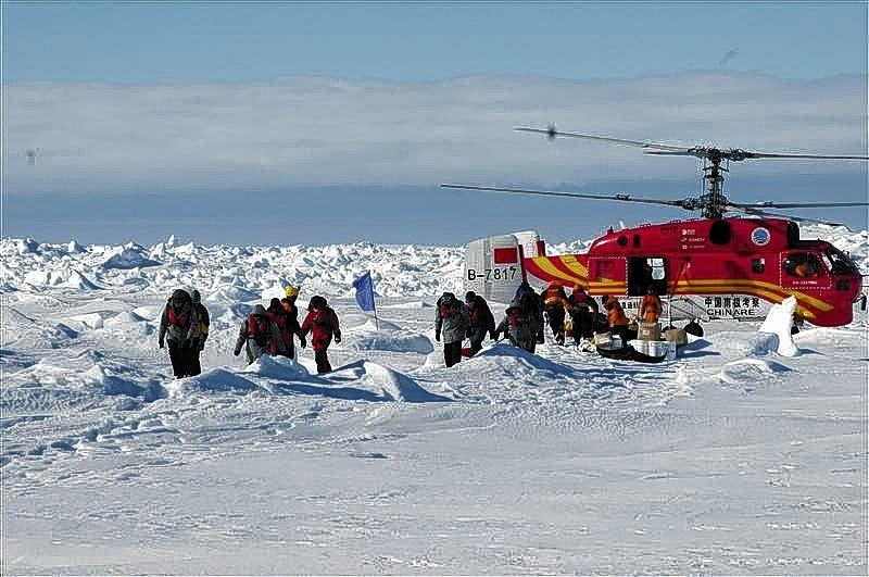 A helicopter from the Xue Long Chinese icebreaker unloads rescued passengers from the ice-bound Russian ship, Akademik Shokalskiy, in East Antarctica.