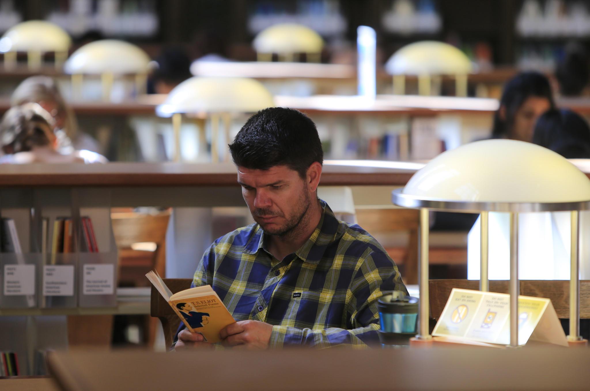 Steven Czifra reads in a UC Berkeley library.