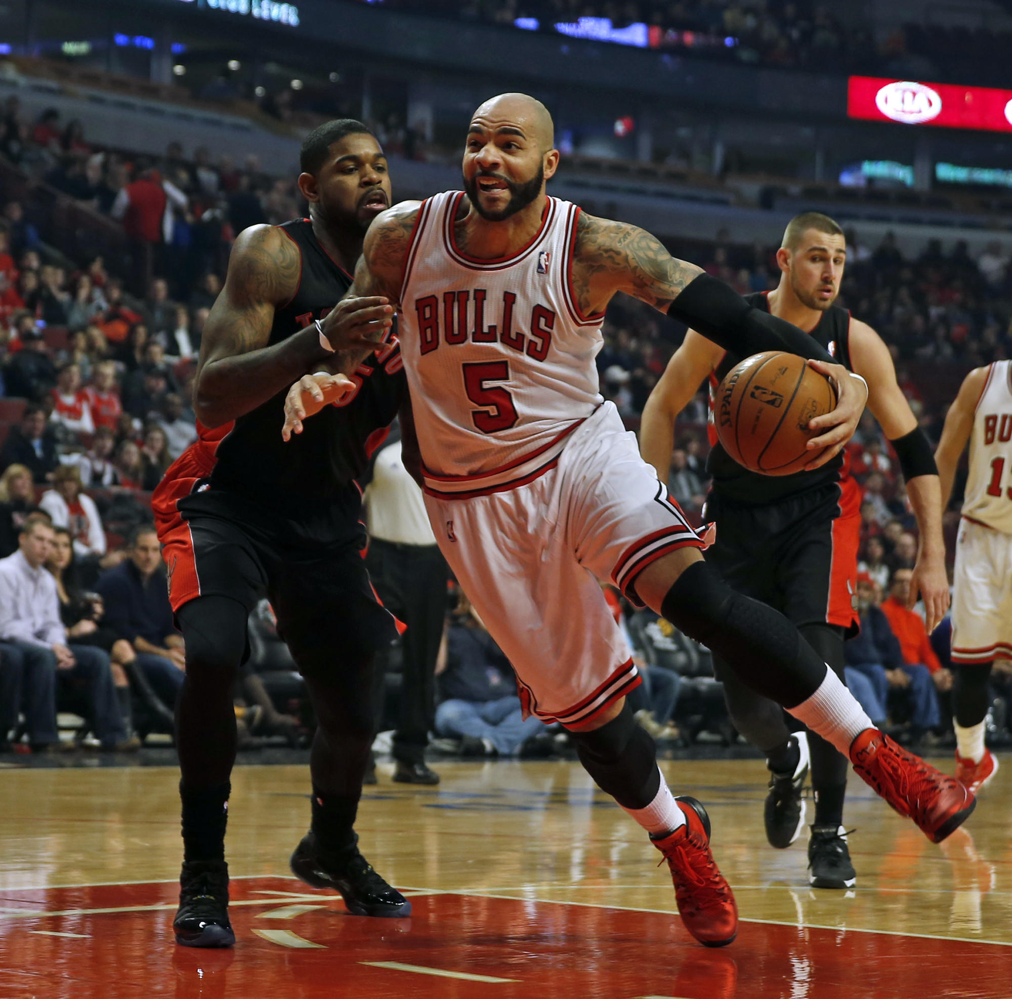 Chicago Bulls' Carlos Boozer drives past Toronto Raptors' Amir Johnson on Dec. 31.