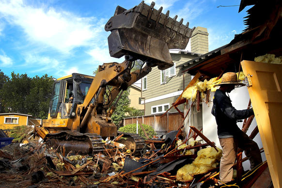 A demolition crew razes a 782-square-foot cottage in Manhattan Beach in October to make way for a 3,300-square-foot Cape Cod mansion.