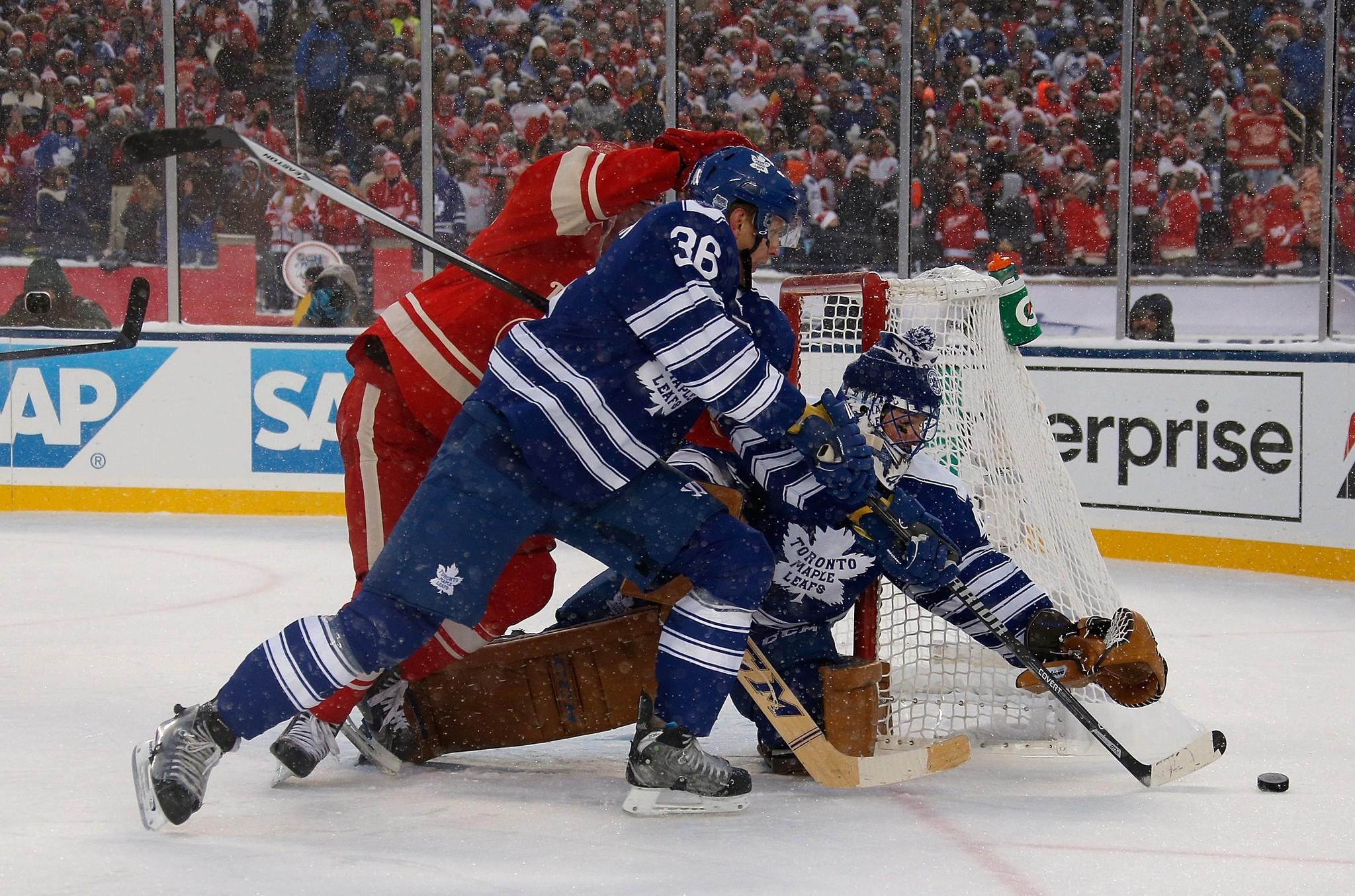 Goalie Jonathan Bernier and Carl Gunnarsson of the Toronto Maple Leafs try to keep the puck from Daniel Alfredsson of the Detroit Red Wings during the 2014 NHL Winter Classic.