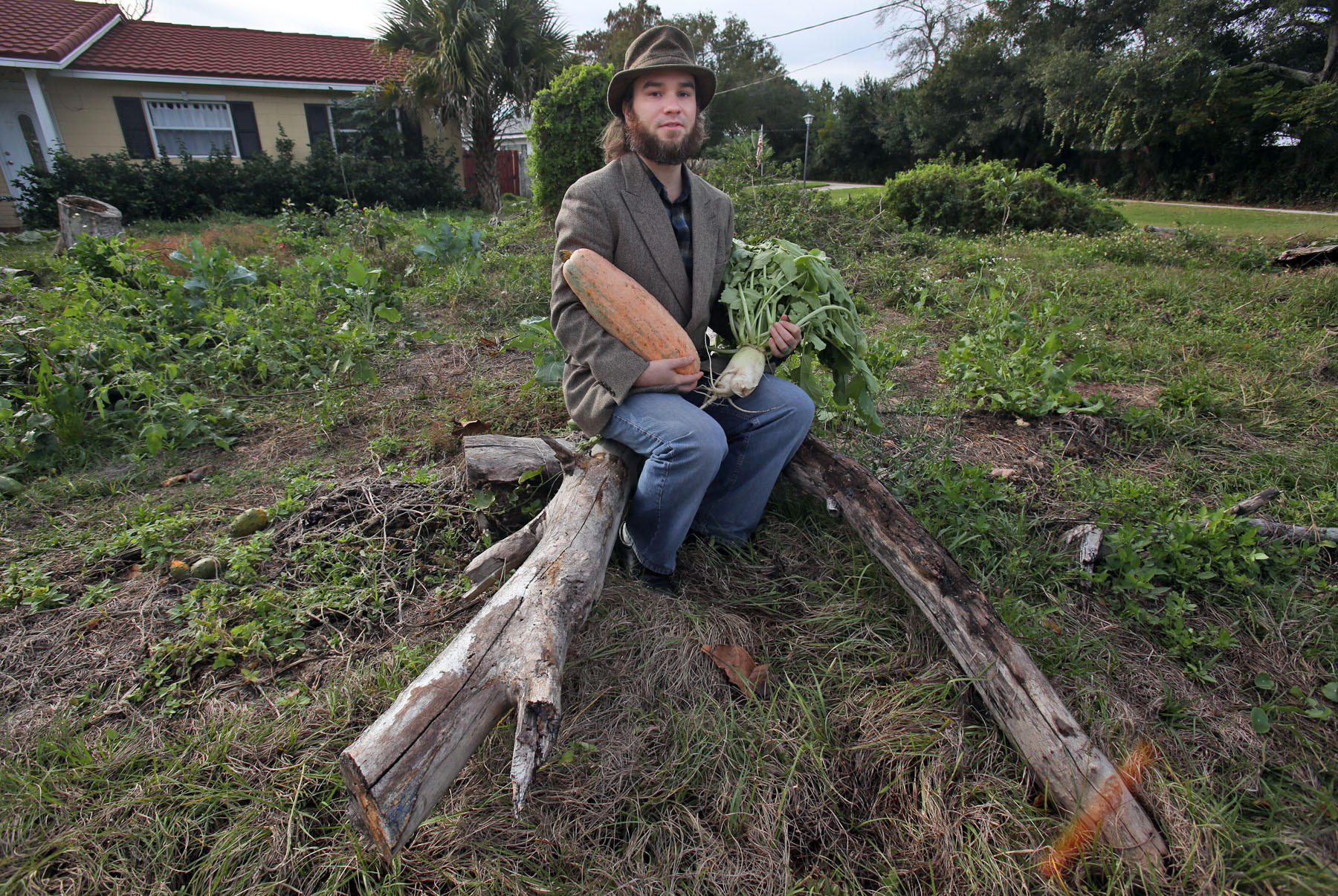Sean Law, 32, holds a squash and a radish Friday, January 3, 2014 in his Longwood frontyard. Law has been fined $130,000 because he has never cut his lawn since moving in - and has left large stumps from trees he cut down. He refuses to clean up the property, saying it's his right because he is merely practicing Florida Friendly Landscaping, something the state encourages.