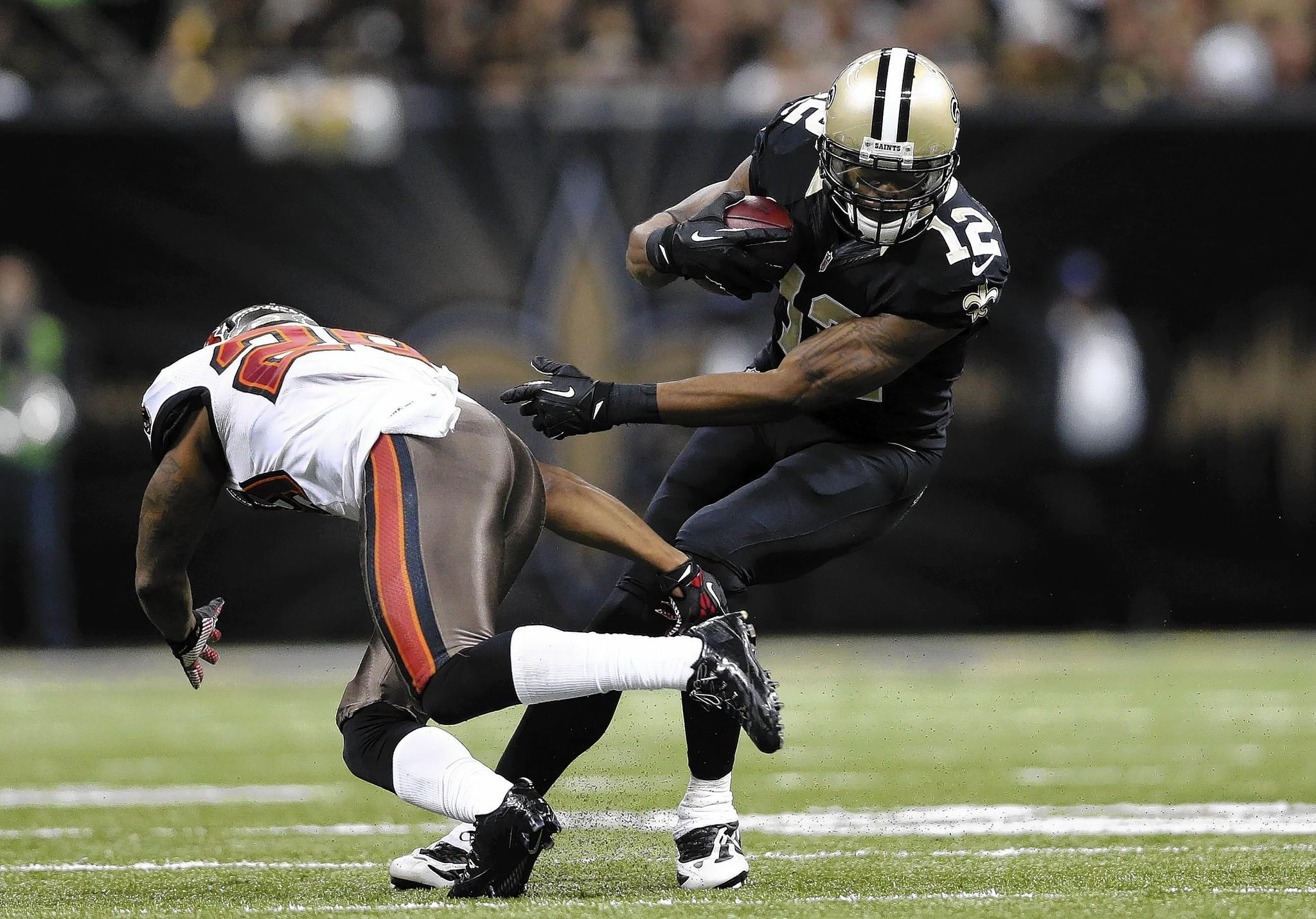 Dec 29, 2013; New Orleans, LA, USA; New Orleans Saints wide receiver Marques Colston (12) carries the ball past Tampa Bay Buccaneers defensive back Rashaan Melvin (28) in the first half at the Mercedes-Benz Superdome.