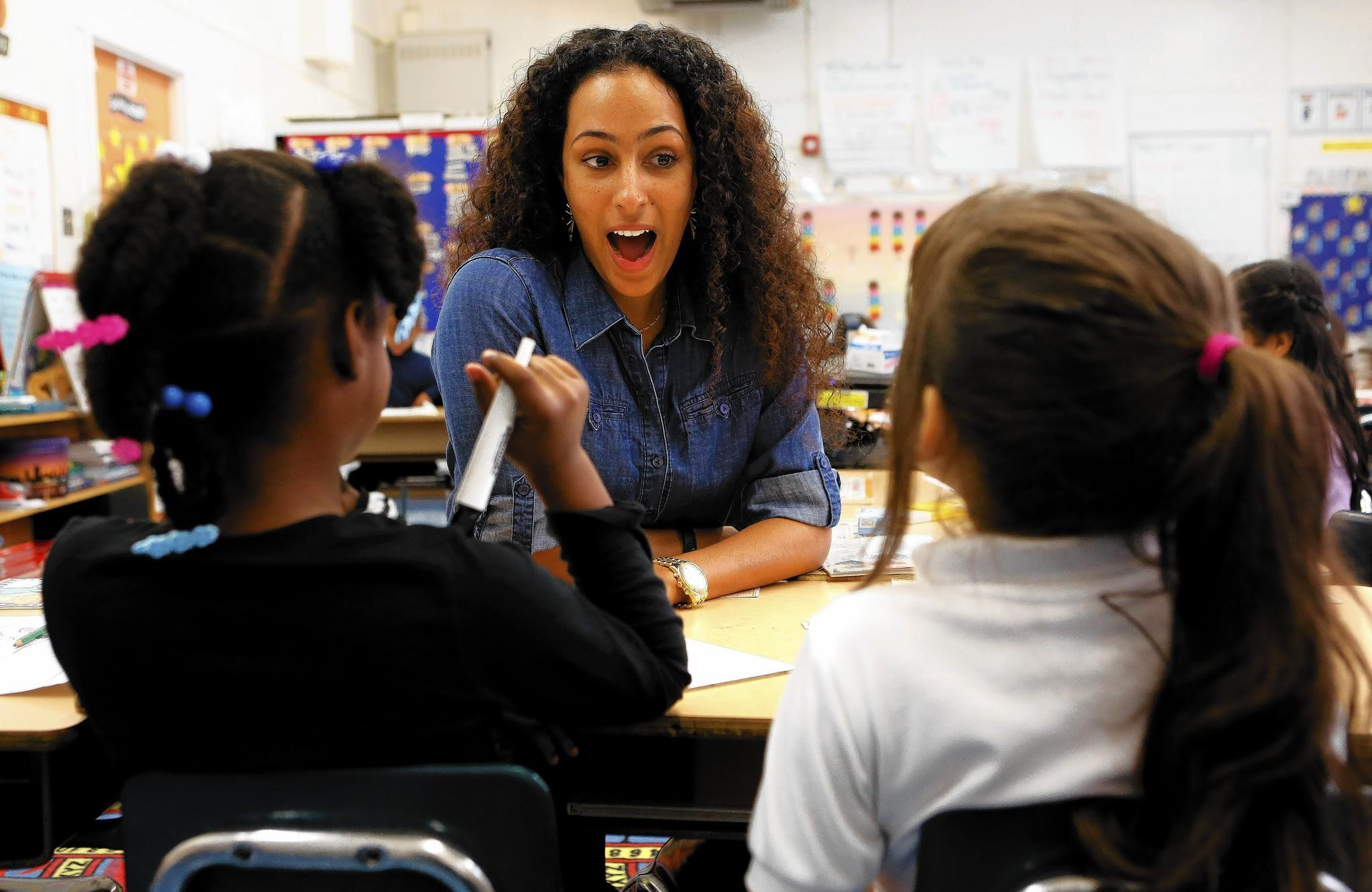 Samantha Pulliam, a first-grade teacher at 24th Street Elementary in Los Angeles, goes over a writing lesson with students. Pulliam, 27, began her teaching career at a charter school because no positions were available in L.A. Unified at the time.