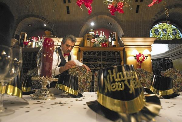 Juvenal Mejia sets the table in the wine cellar for New Year's Eve dinner at the Ritz Restaurant and Garden on Tuesday.