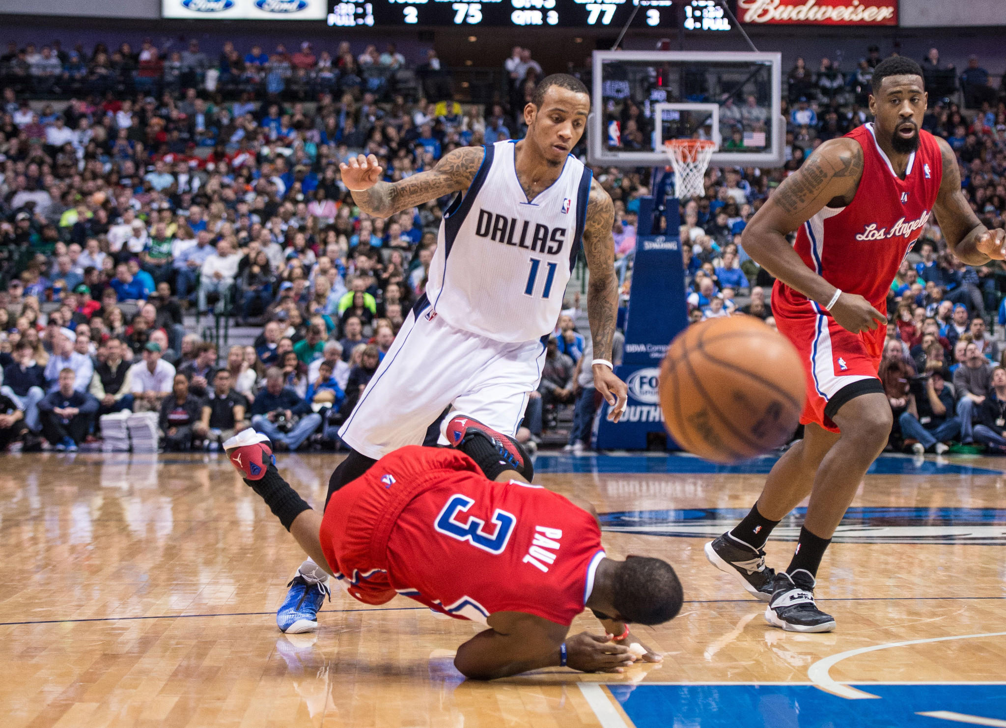 Clippers point guard Chris Paul falls to the court while dribbling past Mavericks shooting guard Monta Ellis during the second half.